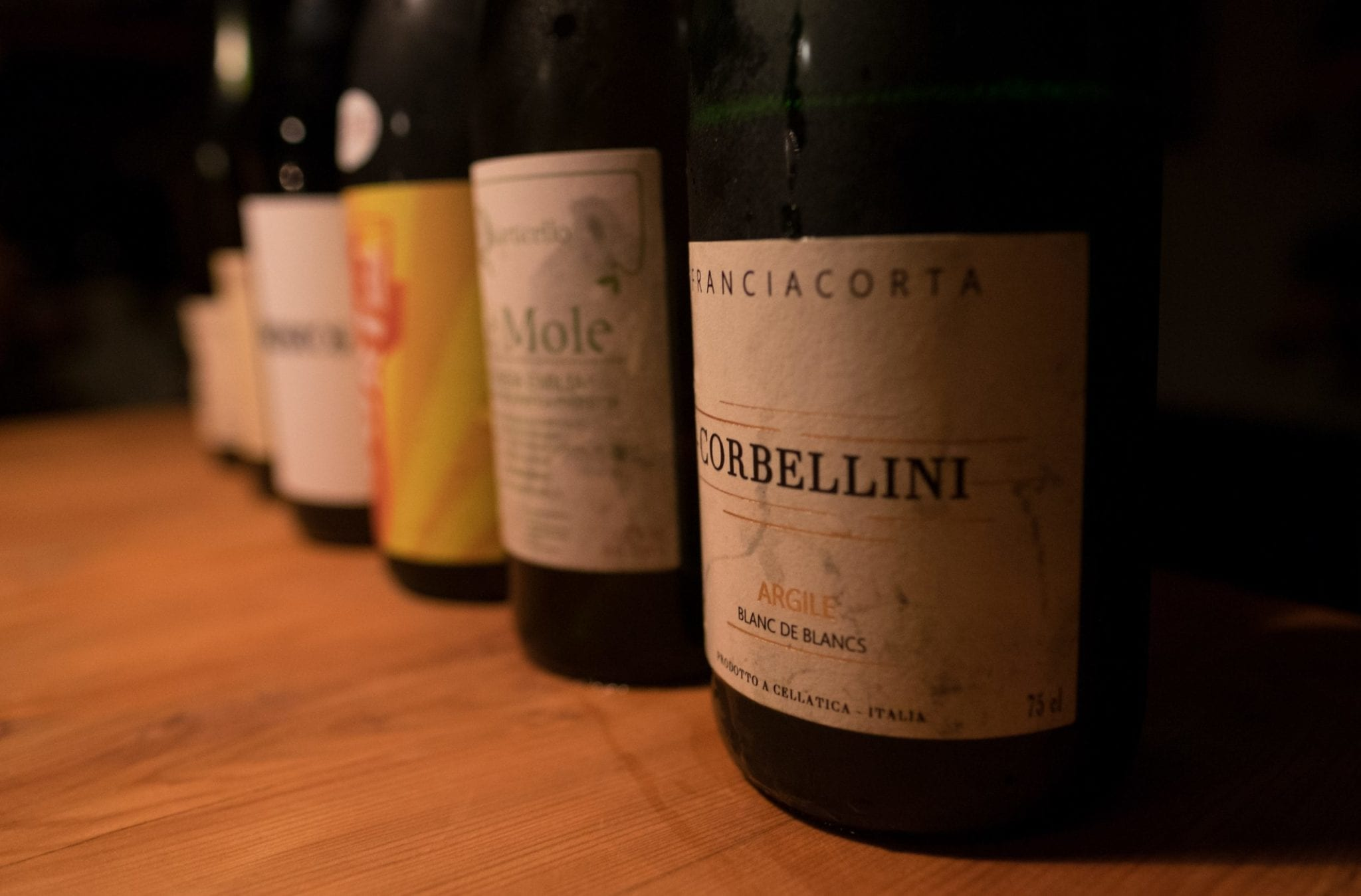 Several wine bottles lined up in a row in dim light, leading with a Franciacorta.