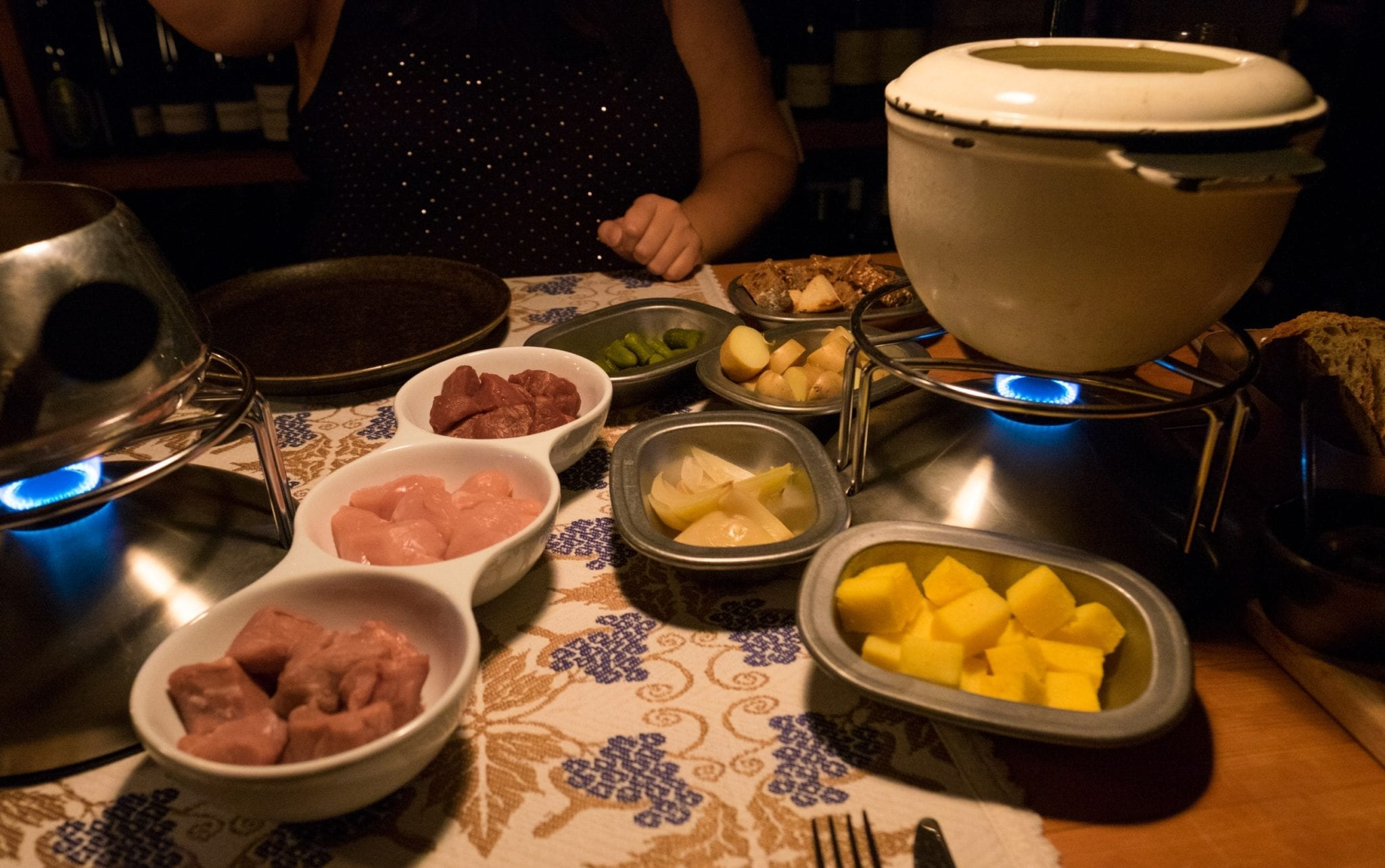 Fondue pots with accoutrements in the front: chicken, veal, and beef, plus polenta, onions, and other small items for dipping.