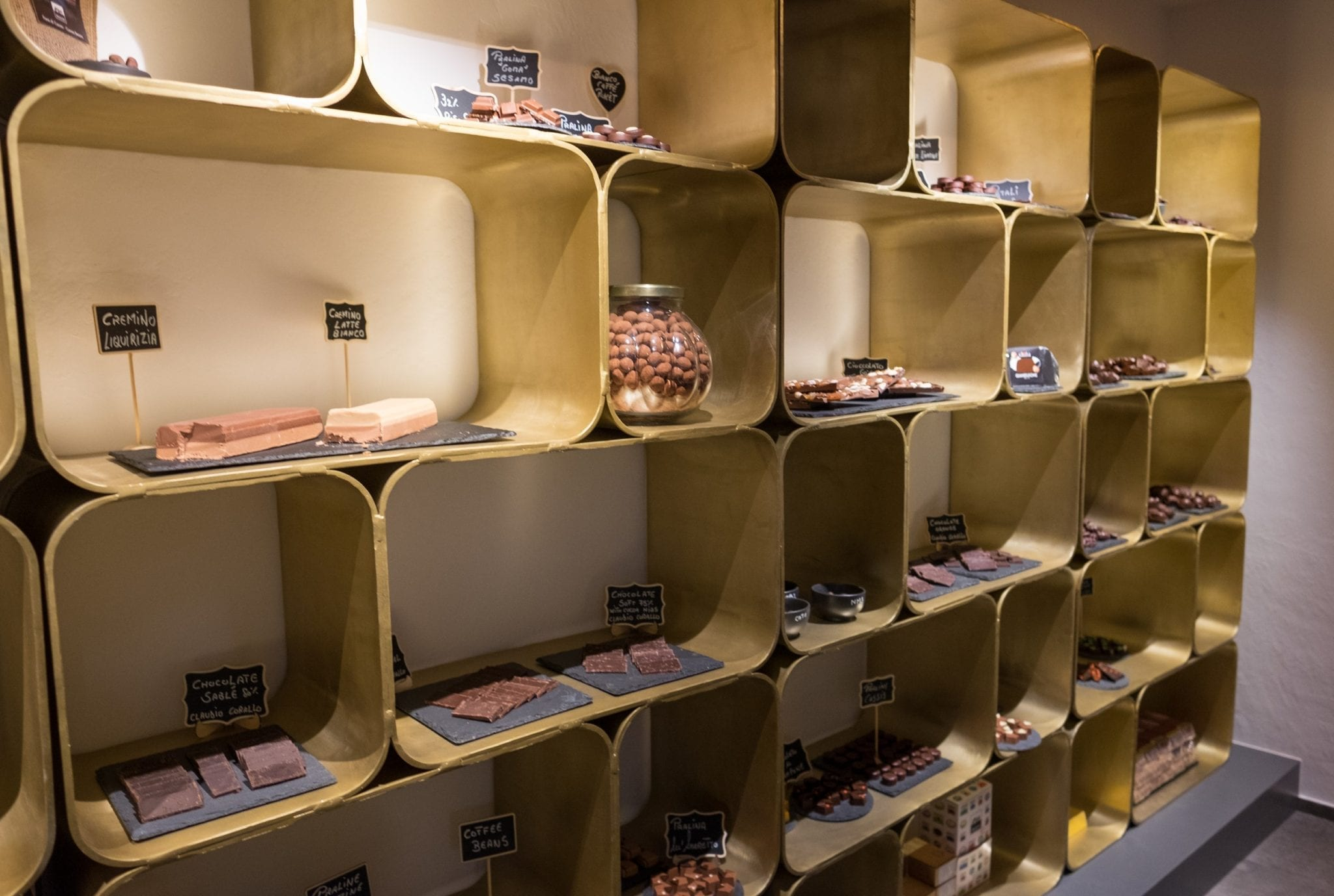 A wall filled with cube-shaped shelves, each filled with different kinds of chocolate.