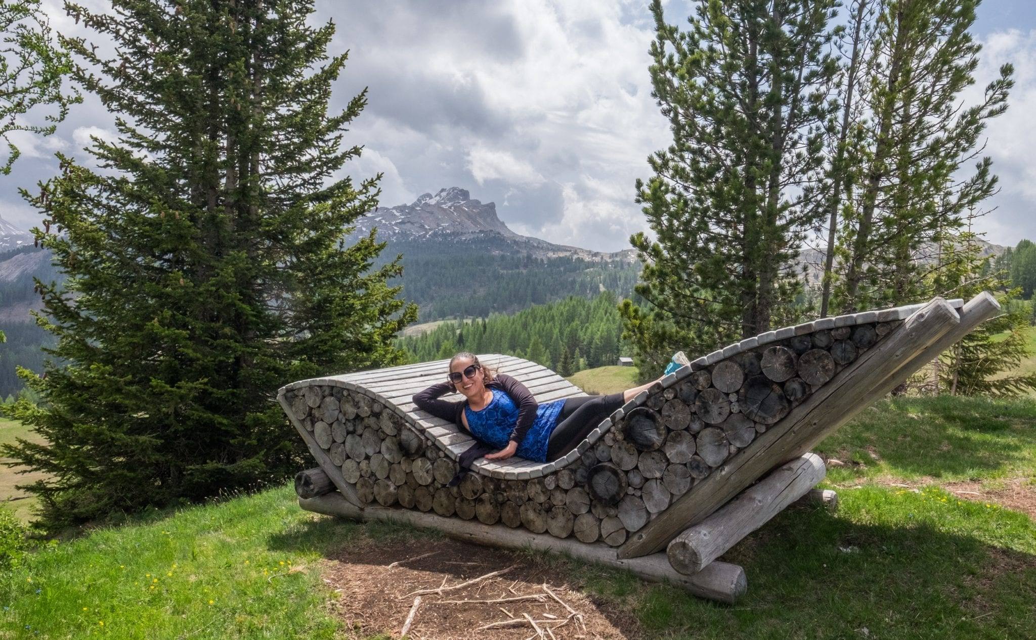 Kate stretches out on a sun lounger in the Dolomites -- it looks like a large chair, and the bottom is made of stacked wood. Trees and a Mountain View are in the distance.