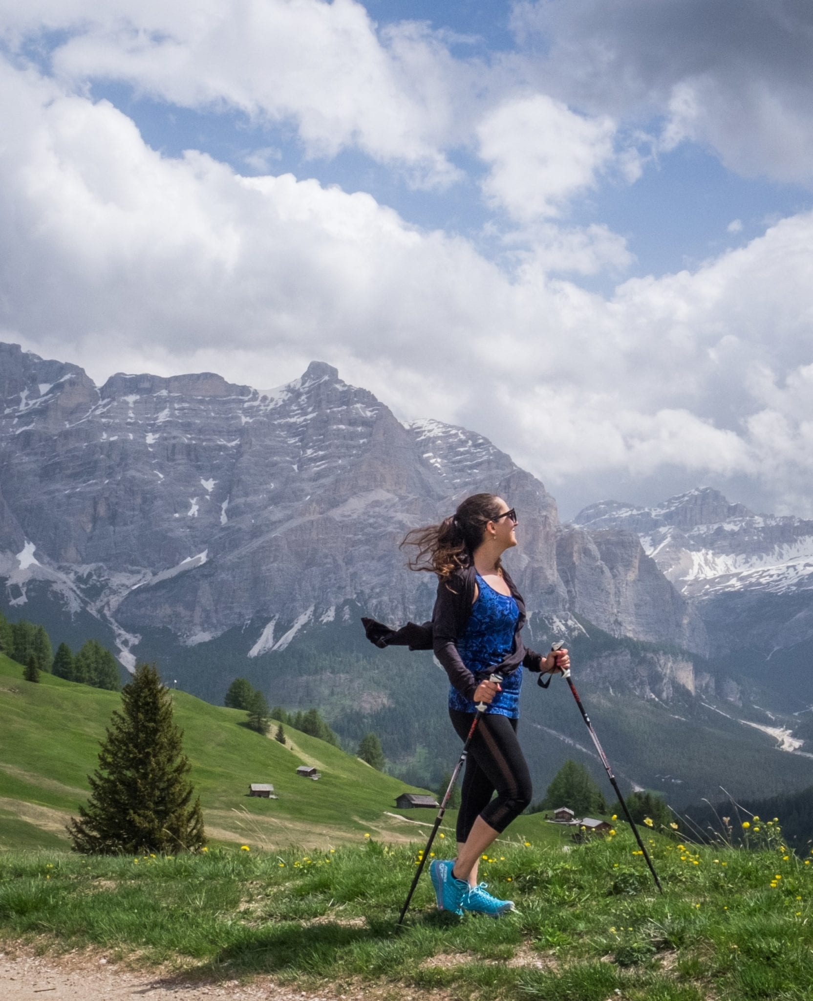 Kate stands on a hill in the Dolomites, holding hiking poles in her hands, illuminated by purple-gray mountains behind her and a cloudy blue and white sky.