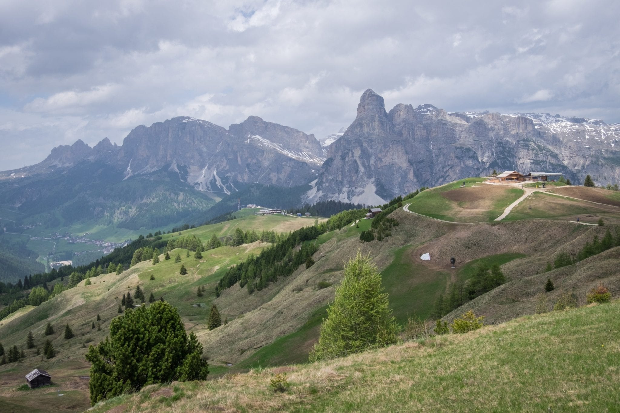 View of the Dolomites: jagged gray peaks in the background and mossy green hills in the foreground. A gray cloudy sky overhead.