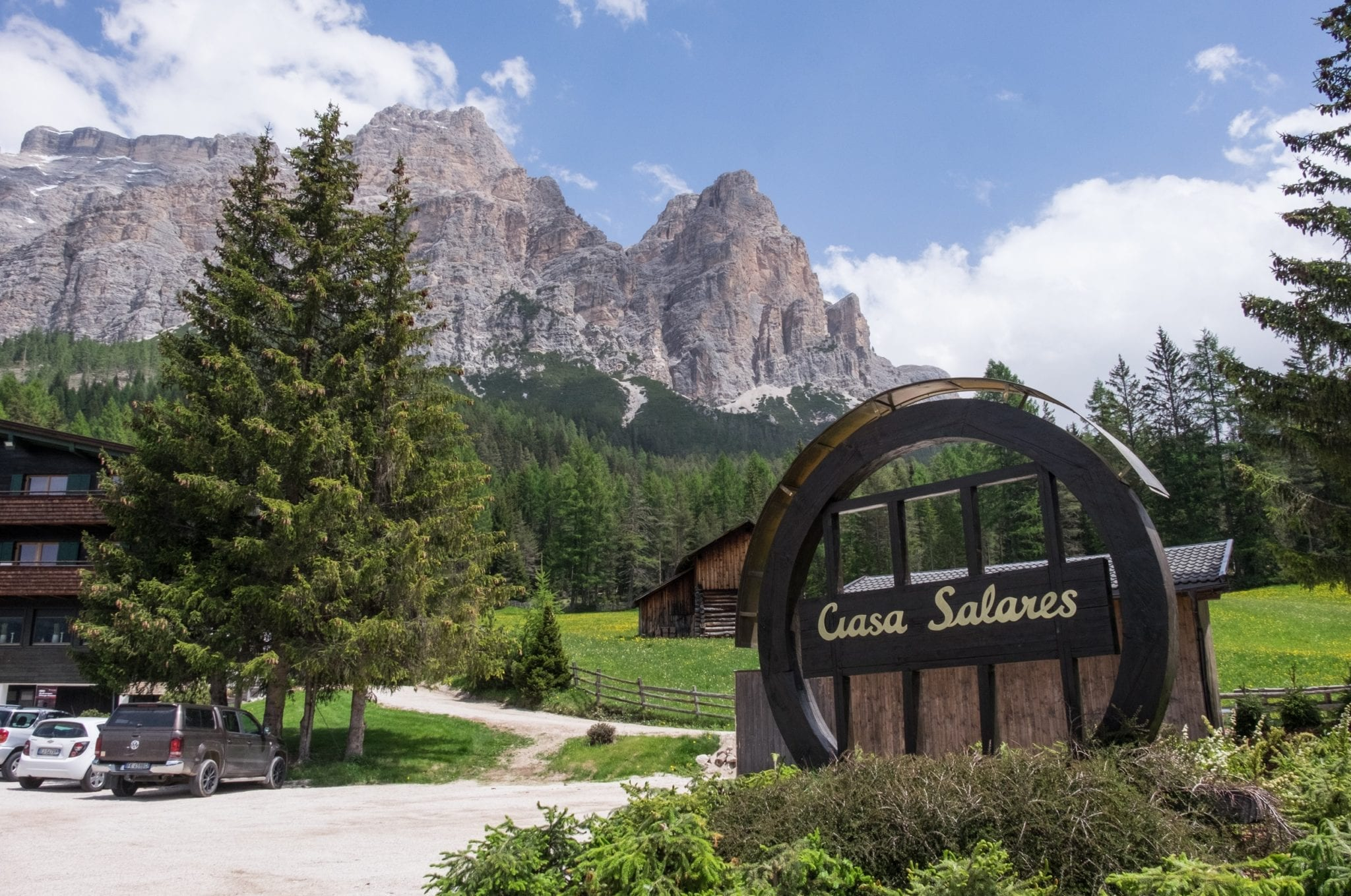 """Ciasa Salares"" is written in a round sign in front of a backdrop of jagged gray mountains, green pine trees, and blue sky."