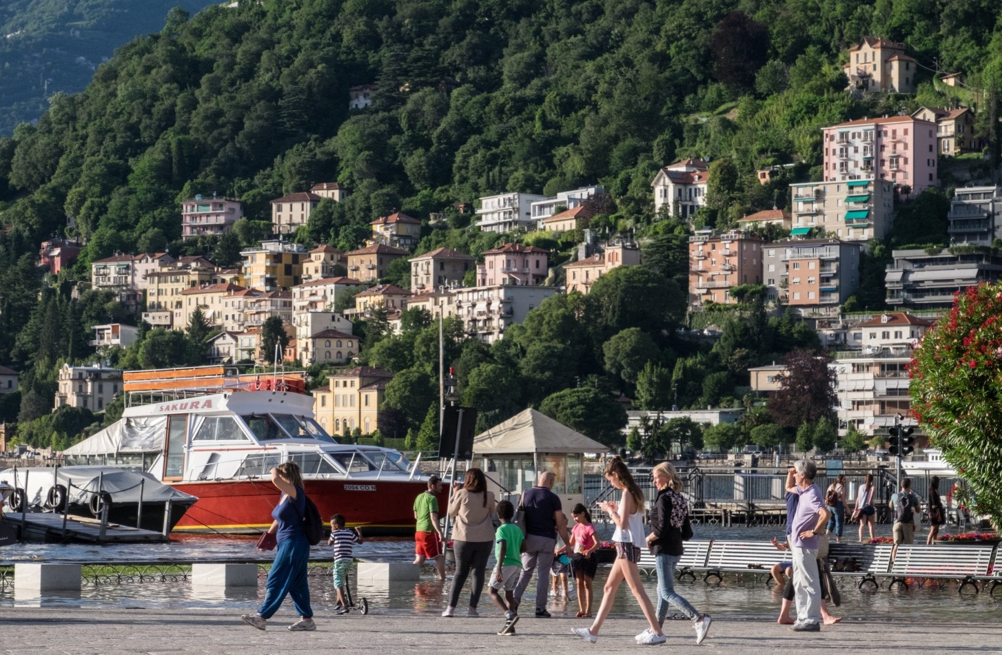 People walk on a piazza in front of buildings nestled into the hills of Lake Como.