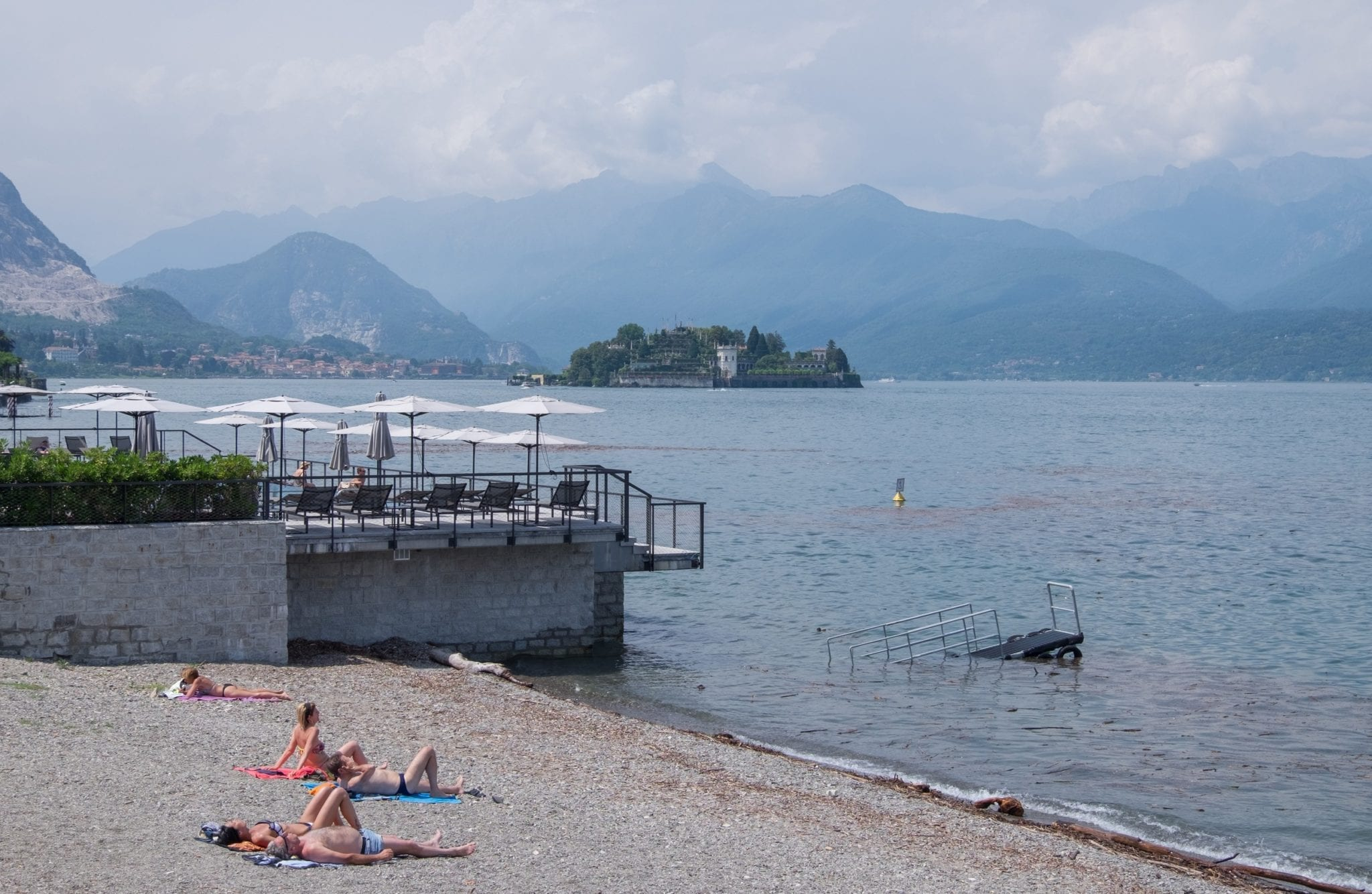 A man and a woman sunbathe on a gray rocky beach overlooking Lake Maggiore, which has an island in the distance and mountains rising up behind it underneath a cloudy sky.