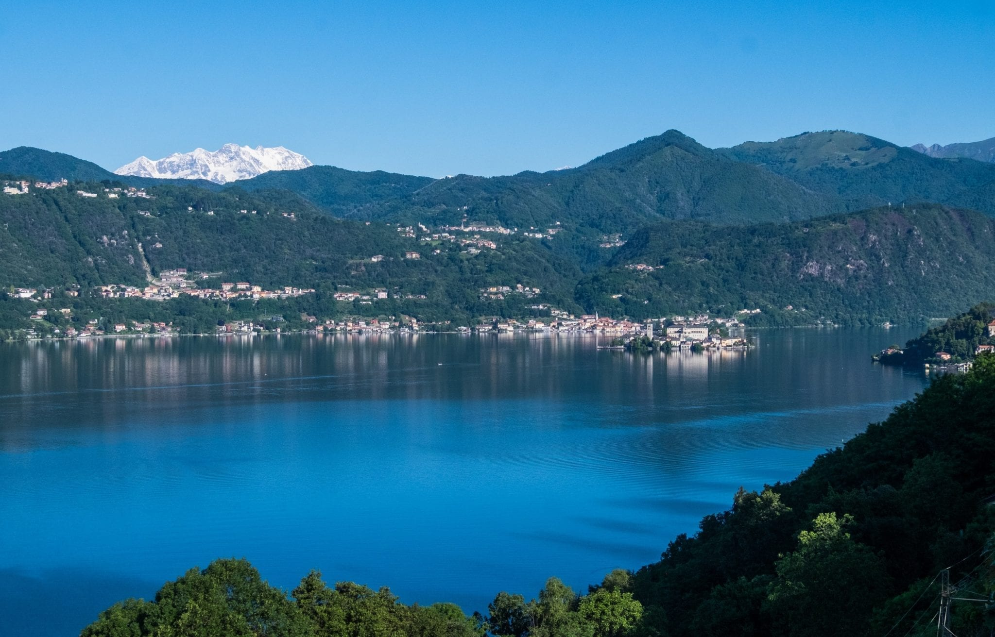 A bright blue Lake Orta with a tiny island in the lake, green mountains on the other side, and a glacier-covered white mountains in the distance,  all underneath a bright blue sky.