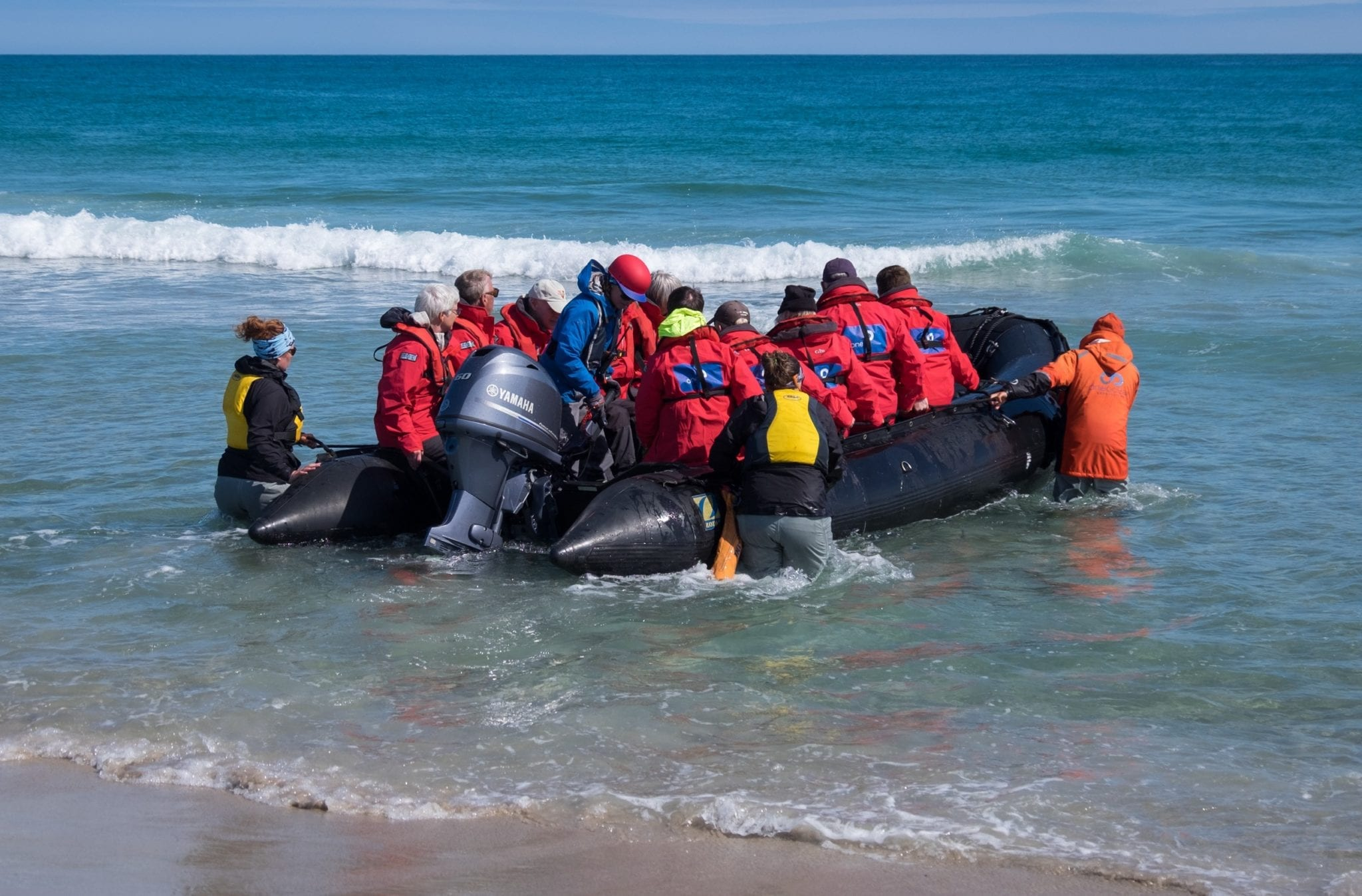 A zodiac full of people launches into the bright blue ocean off Sable Island.