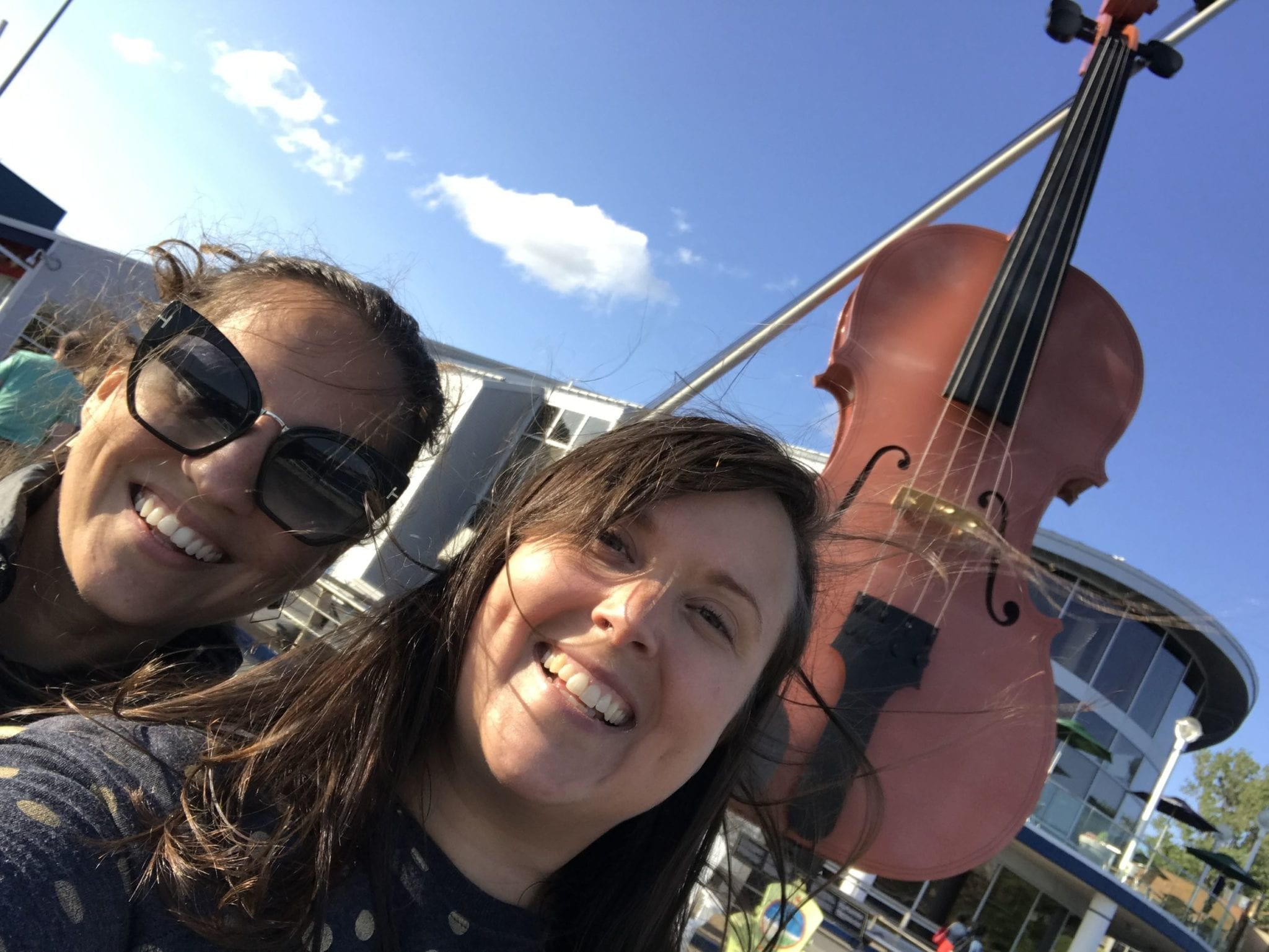 Kate and Cailin pose for a selfie in front of the giant fiddle, standing up in Sydney, Nova Scotia.