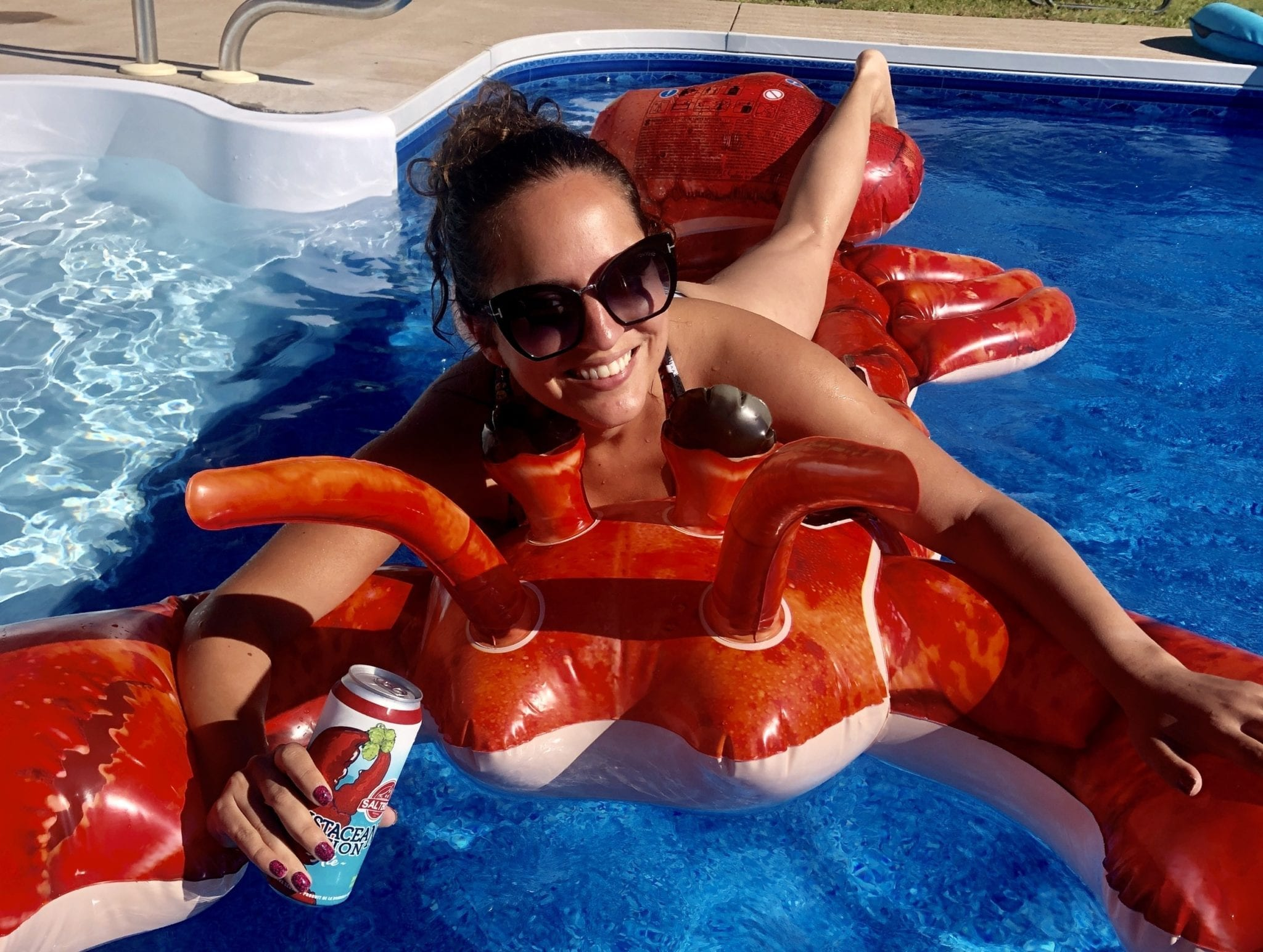 Kate relaxes on a lobster-shaped raft in a pool, holding a lobster-flavored beer.