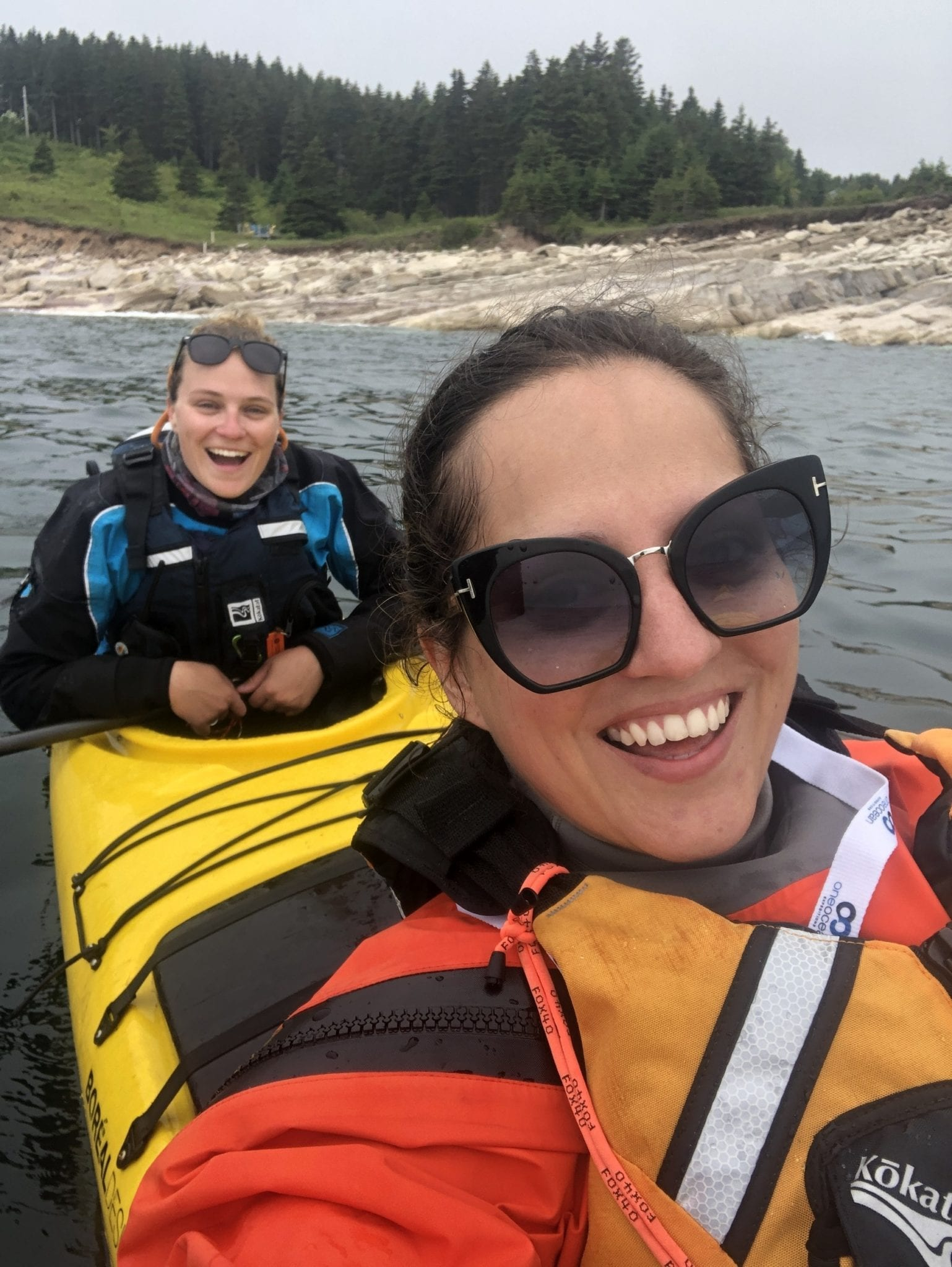 Kate takes a selfie from the front of a kayak as her friend Haley smiles from the back of the kayak.