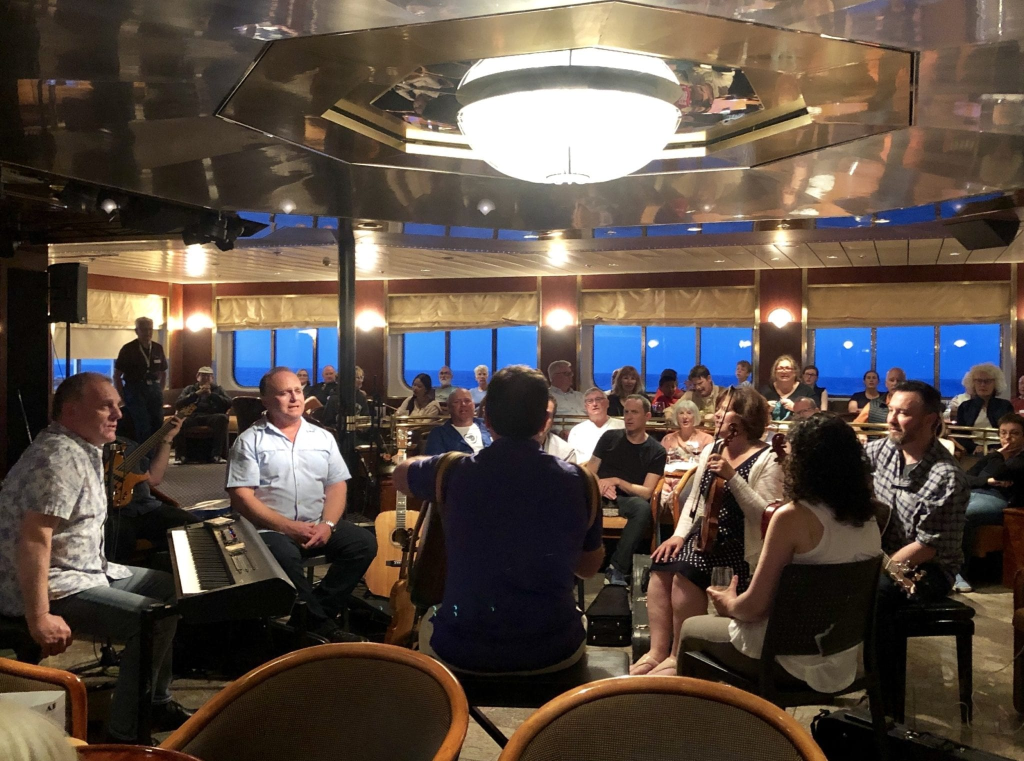The Barra MacNeills band plays with the members sitting in a circle with violins, keyboard, and drums, surrounded by passengers on the cruise ship.