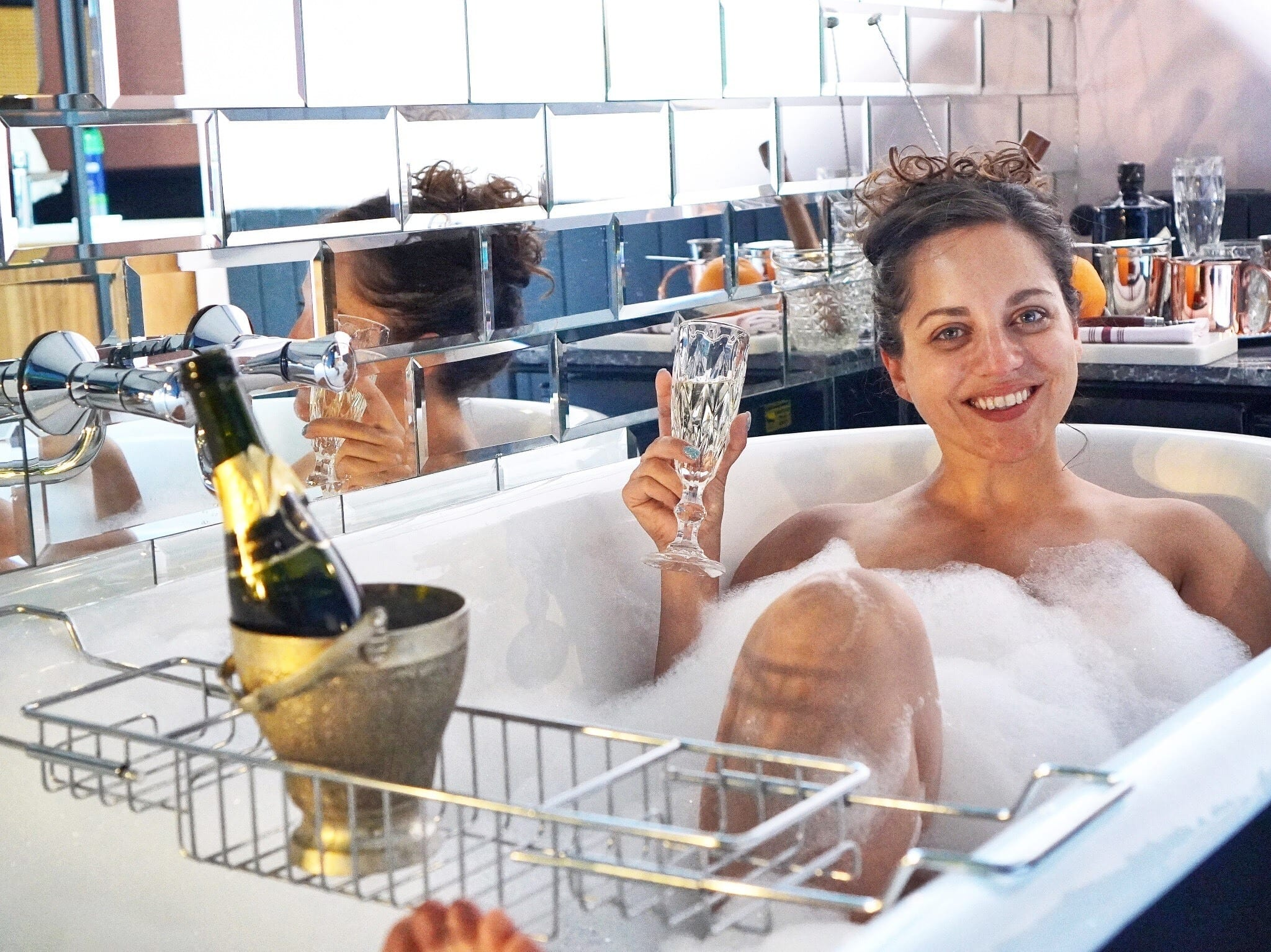 Kate in a bubble bath holding a glass of champagne with her hair up and smiling.
