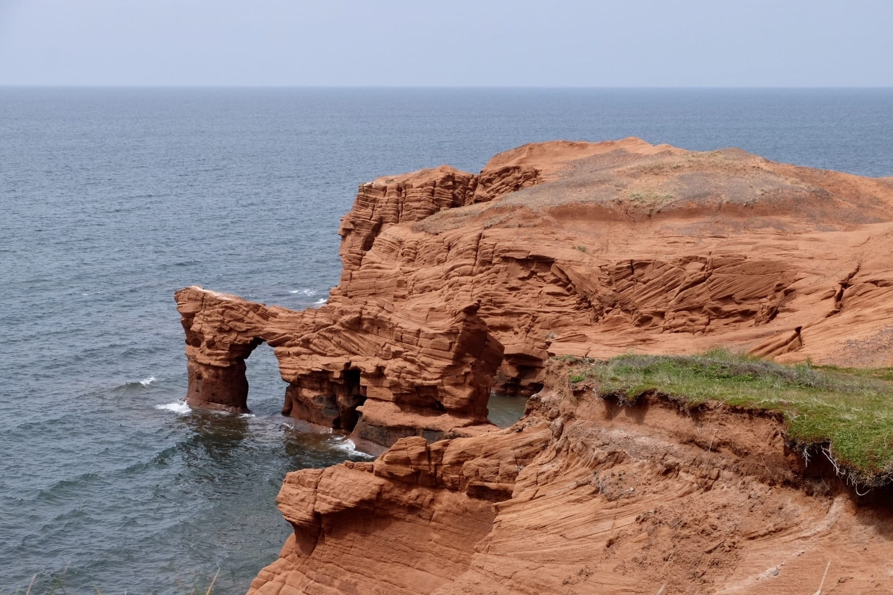 Bright red cliffs in fall into the ocean.