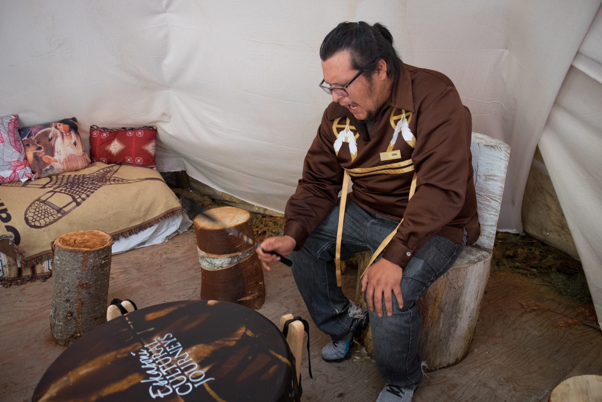 A Mi'kmaq man plays a drum and sings.