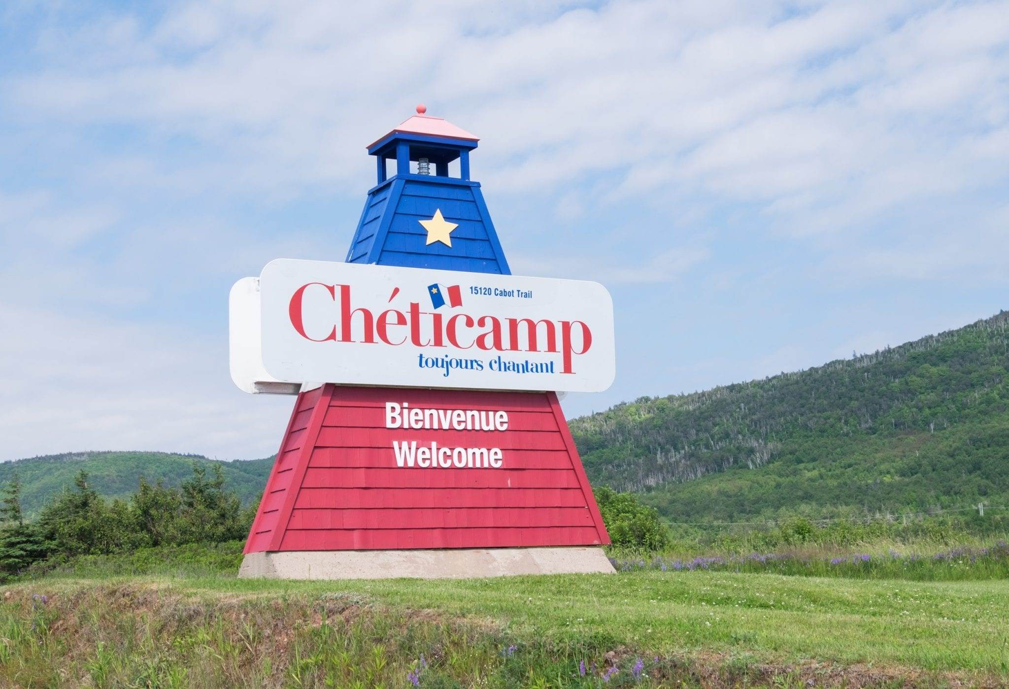 A red and blue Cheticamp sign shaped like a lighthouse.