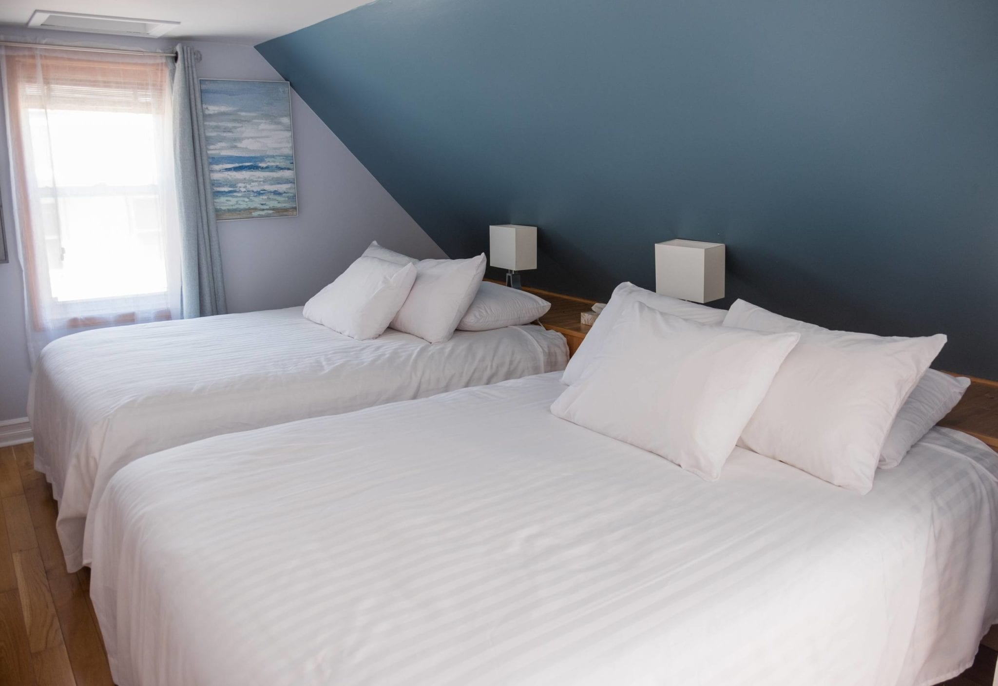 Two queen beds in white bedding with lots of pillows in Silver Linings Inn, Cheticamp, Nova Scotia.