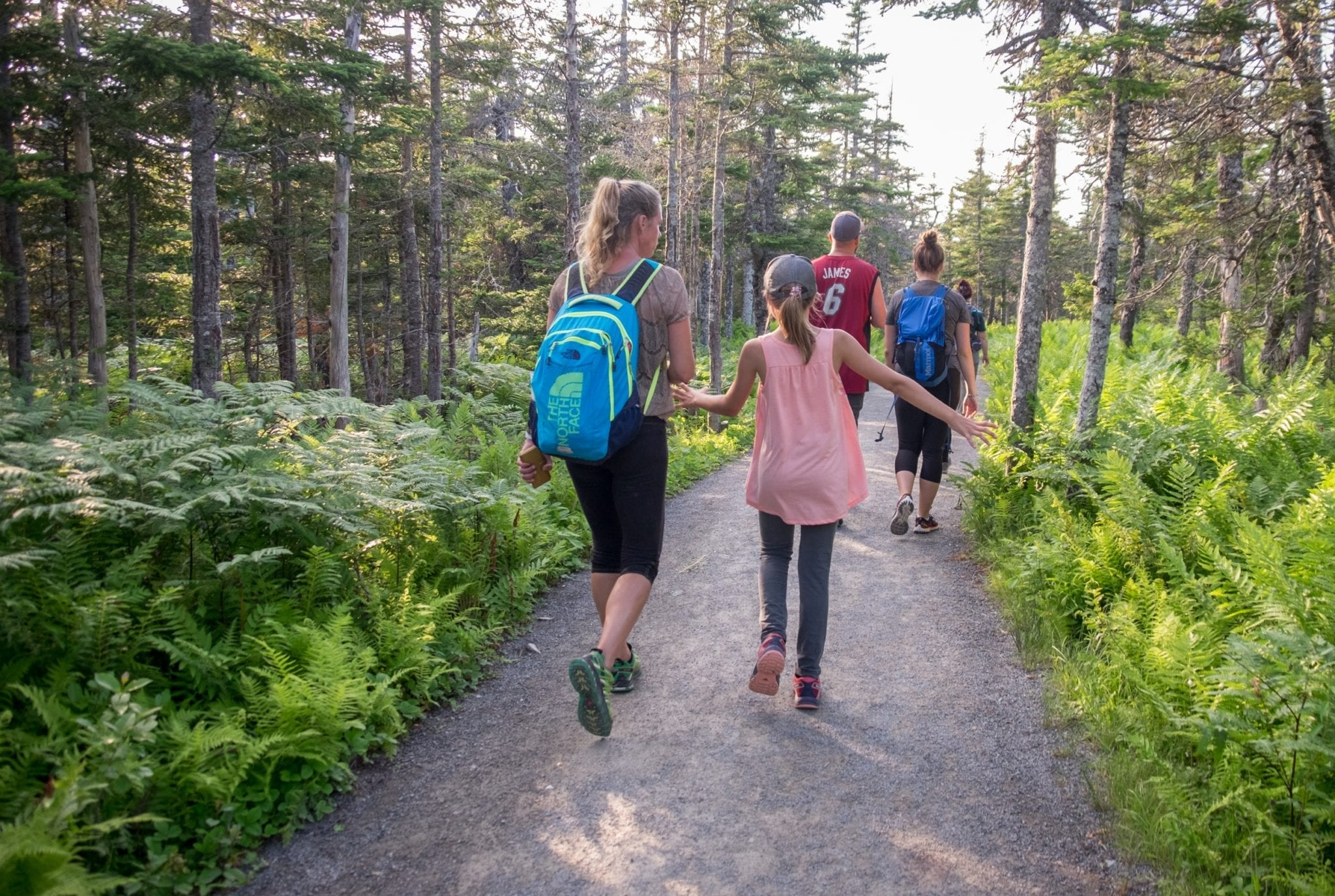 A mother and daughter walking along a forested path in Cape Breton Highlands National Park.