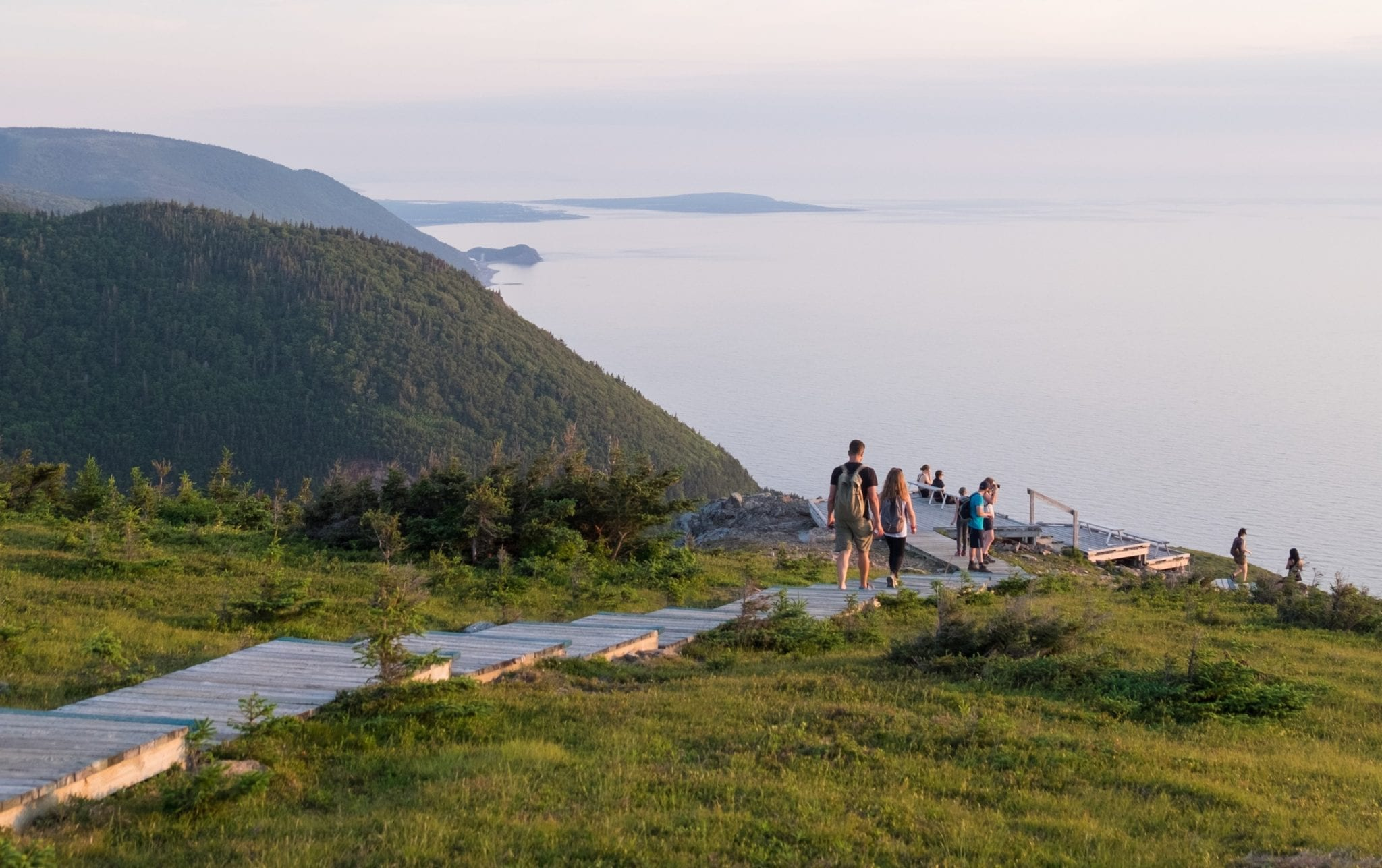 People walking down a staircase built into the hills at Cape Breton Highlands National Park.