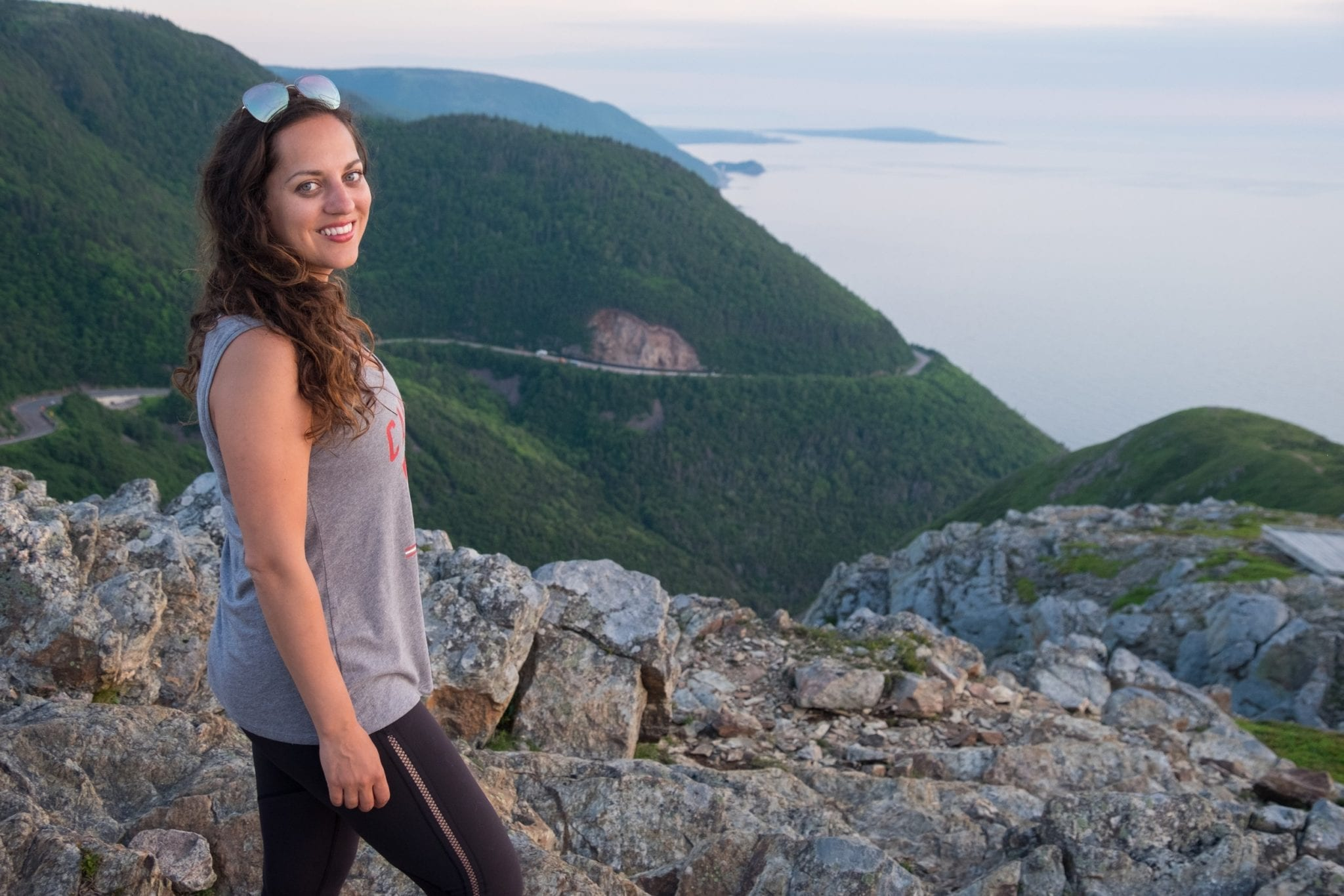 "Kate standing in front of the mountains wearing a ""Canada 2019"" tank top in Cape Breton Highlands National Park."