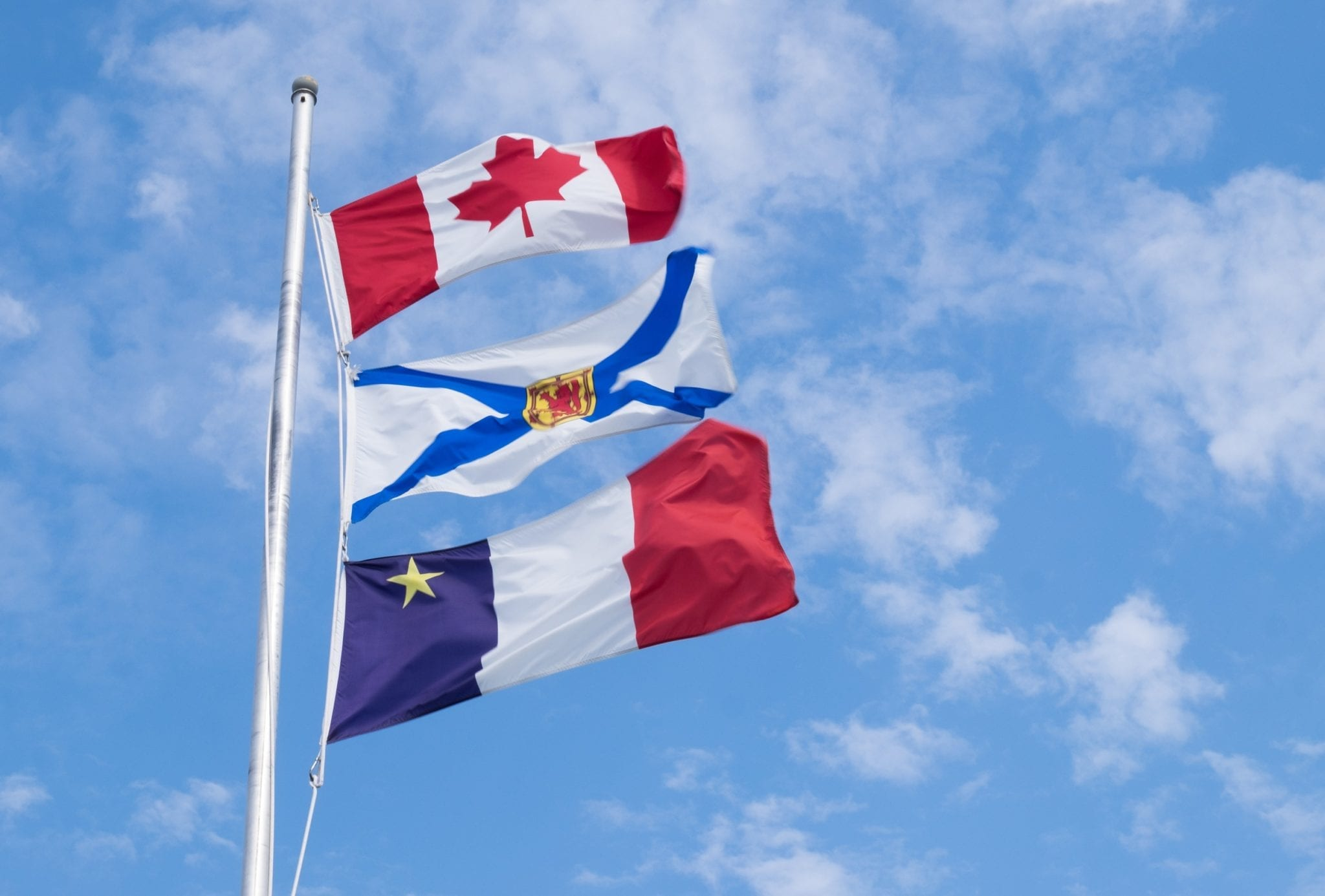 The Canadian, Nova Scotian, and Acadian flags set against a blue sky.