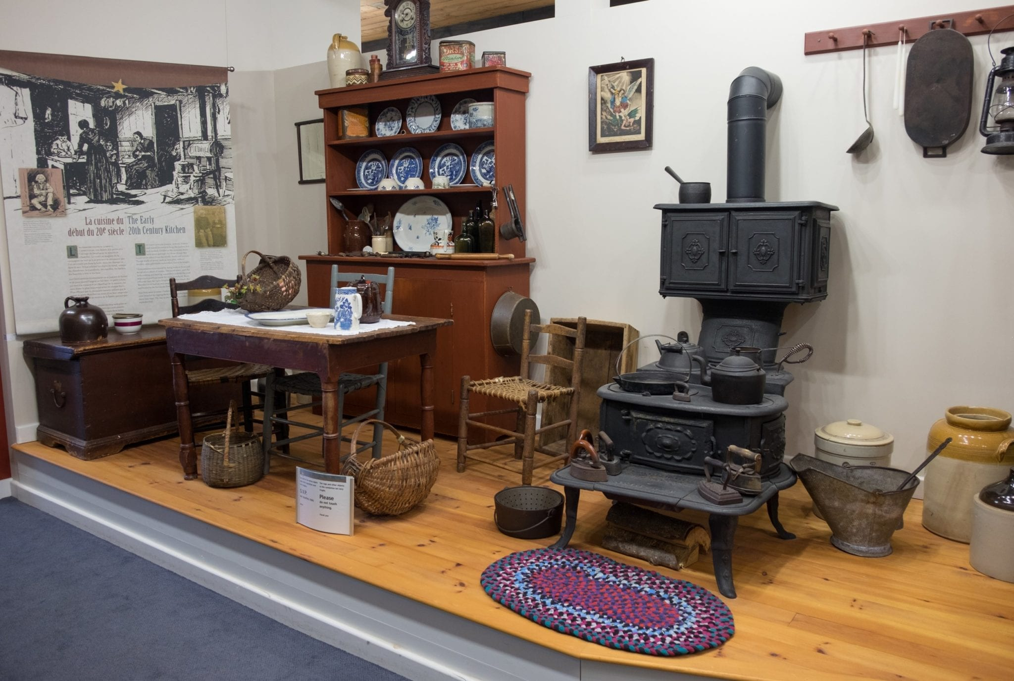 A recreation of an Acadian home at Les Trois Pignons with a china cabinet, wooden dining table, iron stove, and braided rug on the ground.