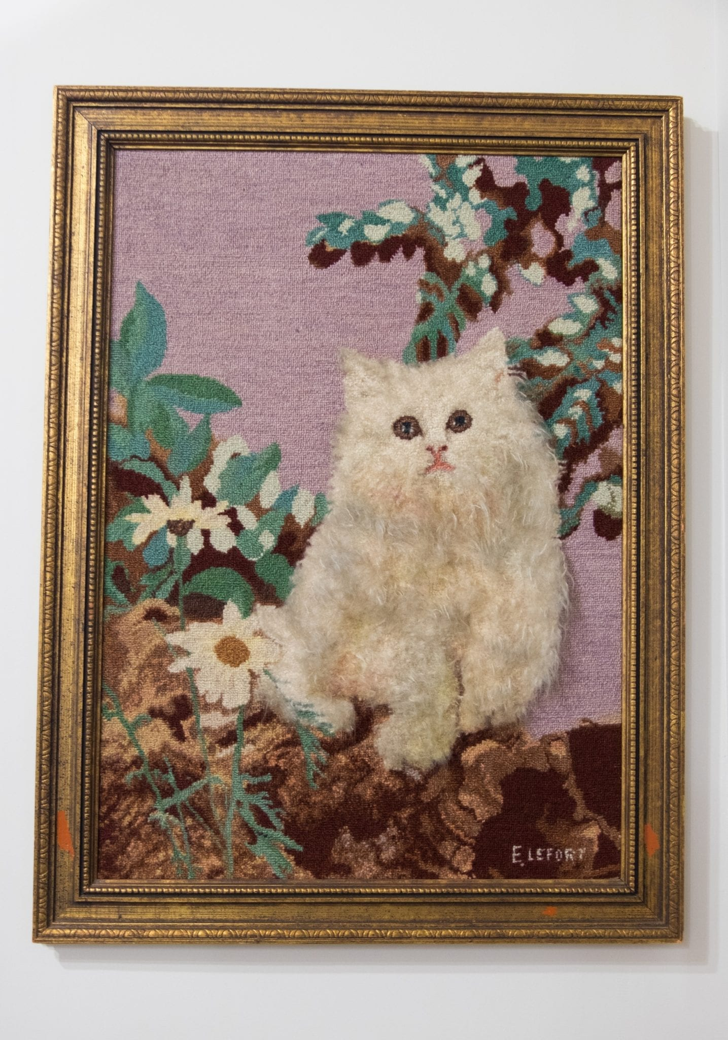A hooked rug with a white Persian cat on it.