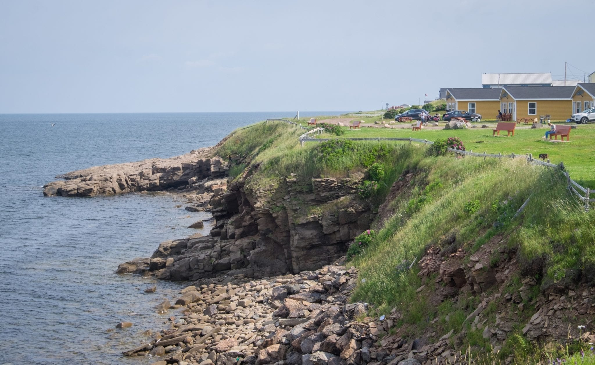 A rocky coastline falls into the sea. On the top is grass, two yellow cottages, benches, and picnic tables.