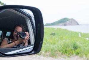 In the rearview mirror, you see Kate taking a photo with her DSLR camera. In the distance is a rock formation in the ocean.