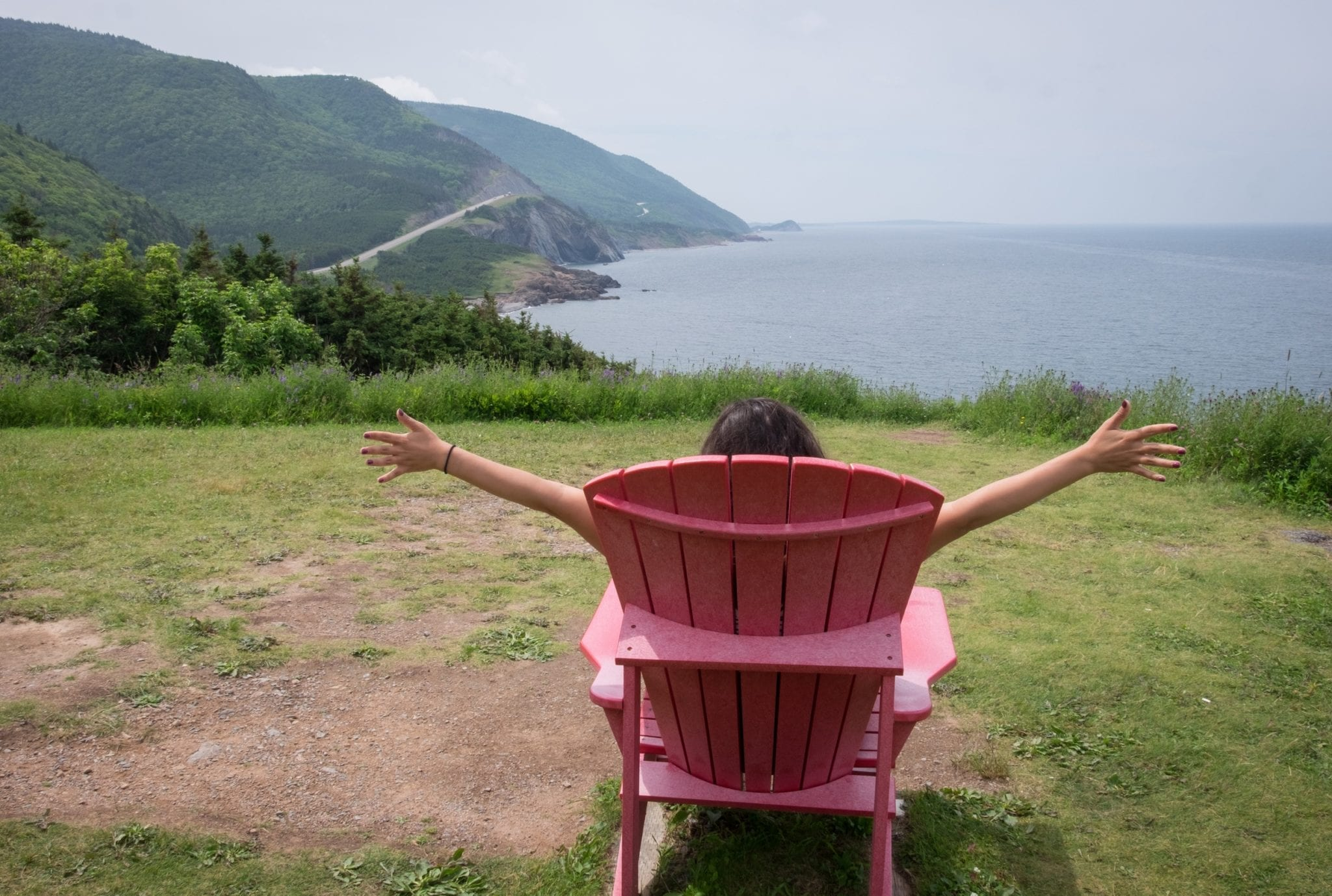 Kate sits in a red chair and has her arms up giving double thumbs ups. In front of her are hills, winding roads, and the ocean at Cape Breton Highlands National Park.