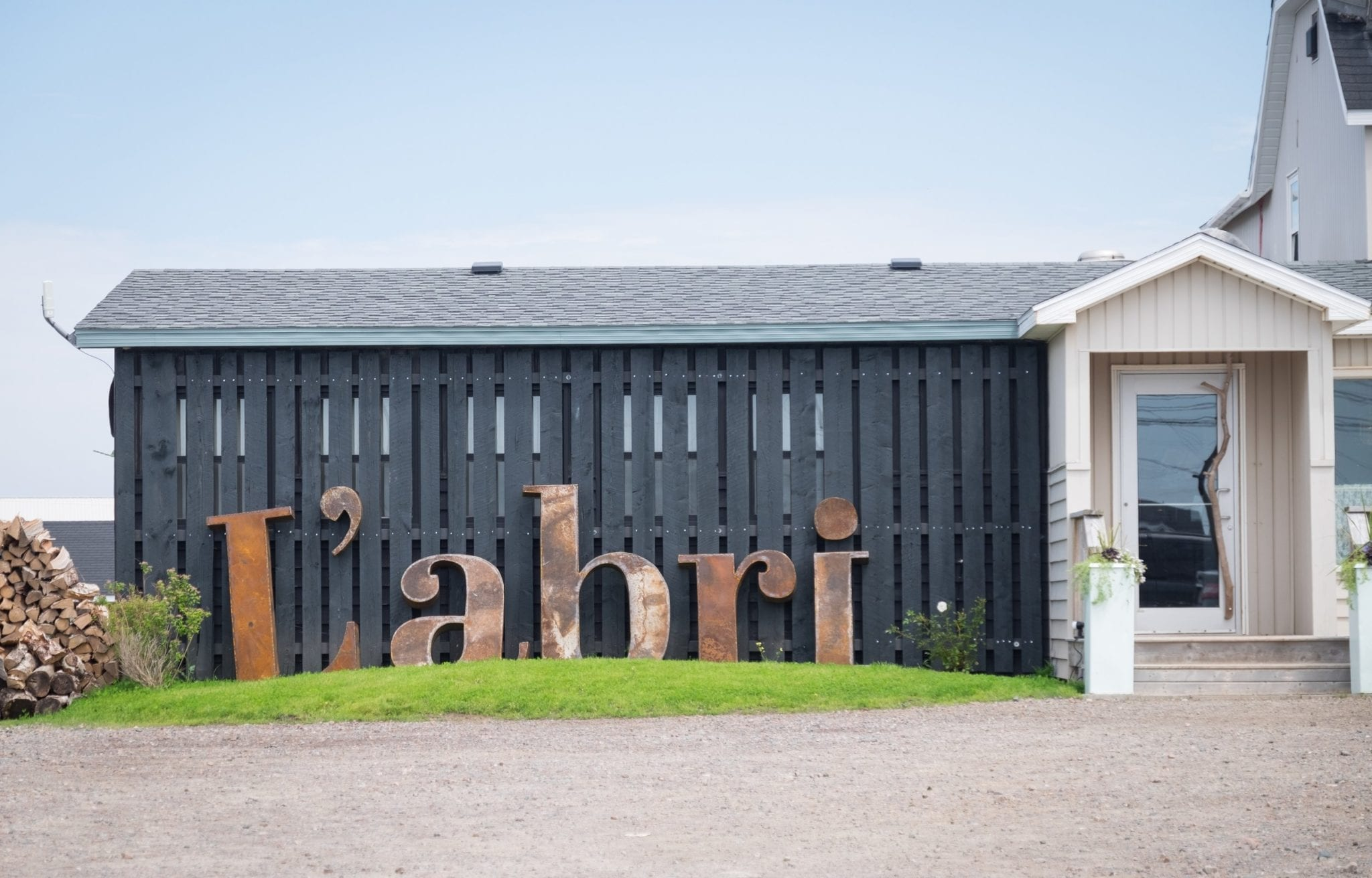 Giant letters reading L'abri in front of a one-story restaurant