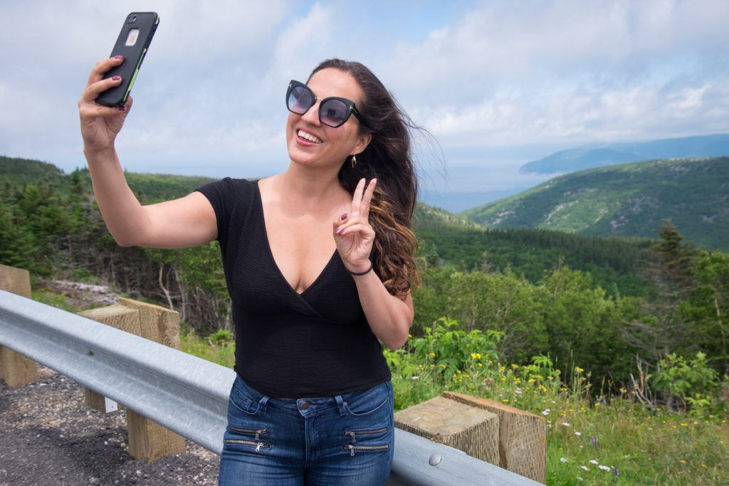 Kate wears large sunglasses and takes a selfie in front of hills and oceans at Cape Breton Highlands National Park
