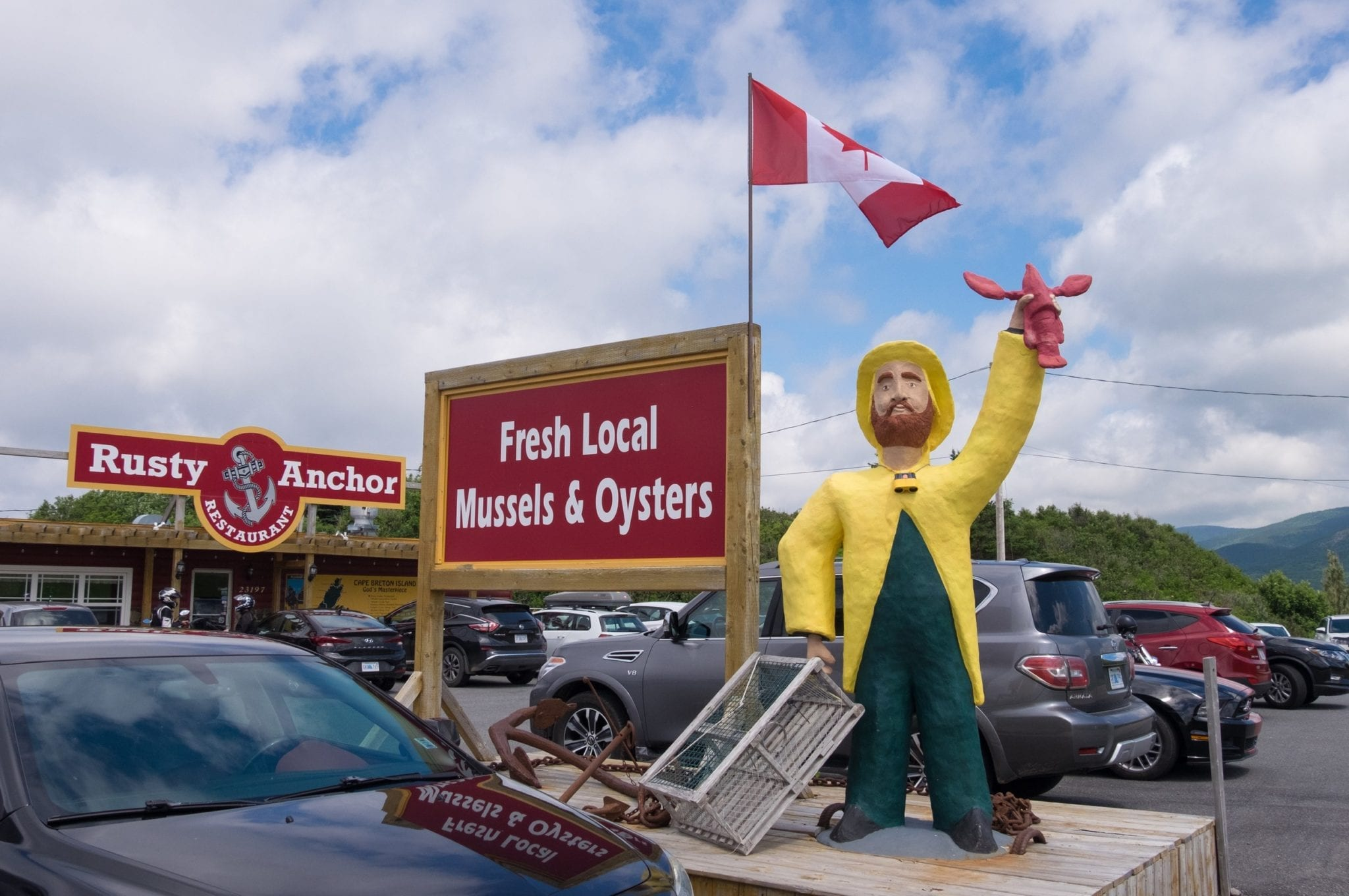 A wooden fisherman holds up lobster outside the Rusty Anchor restaurant in front of a sign that reads Fresh Local Mussels and Oysters.