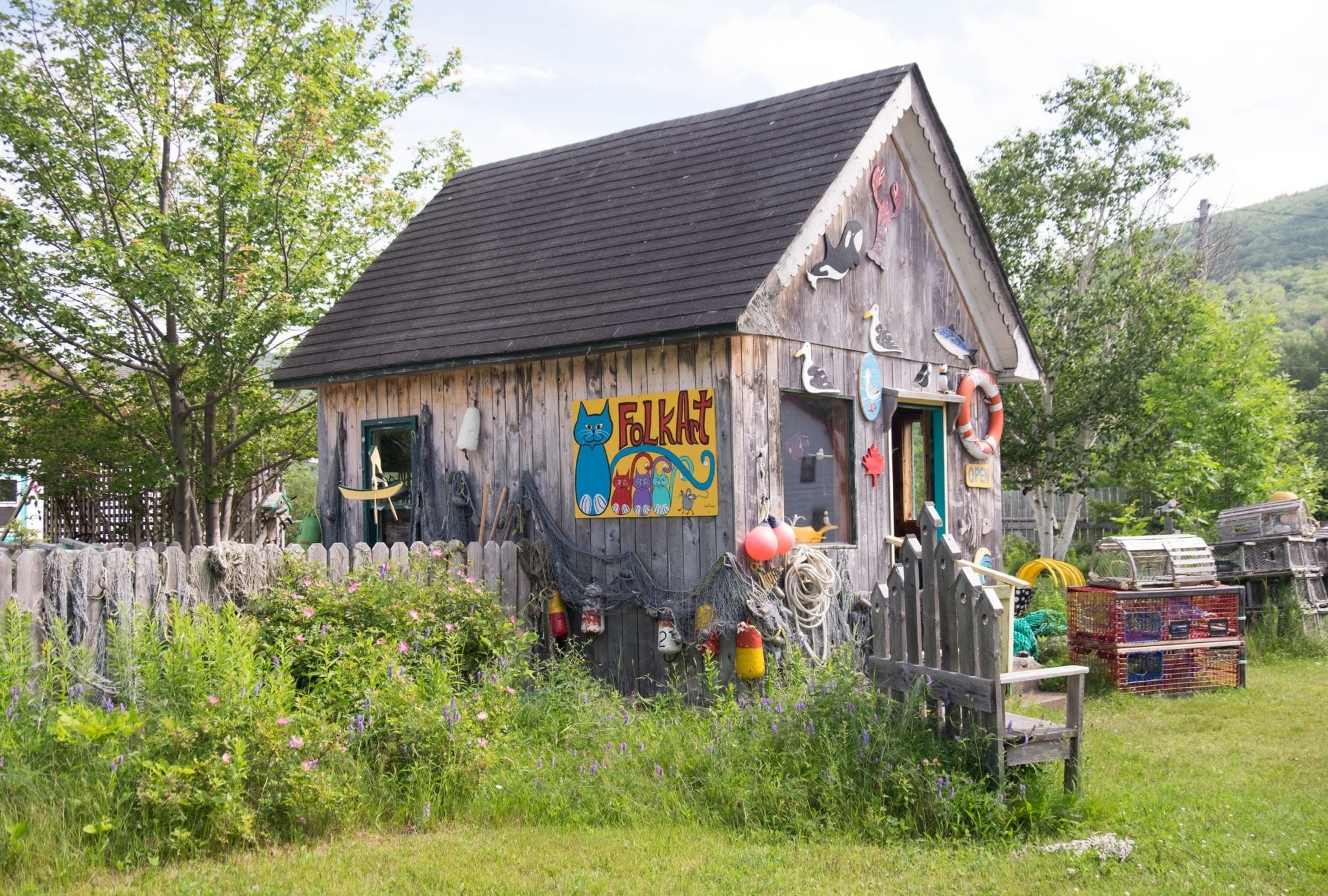 A small cabin covered with wooden art and brightly painted signs, surrounded by a fence overgrown with grass.