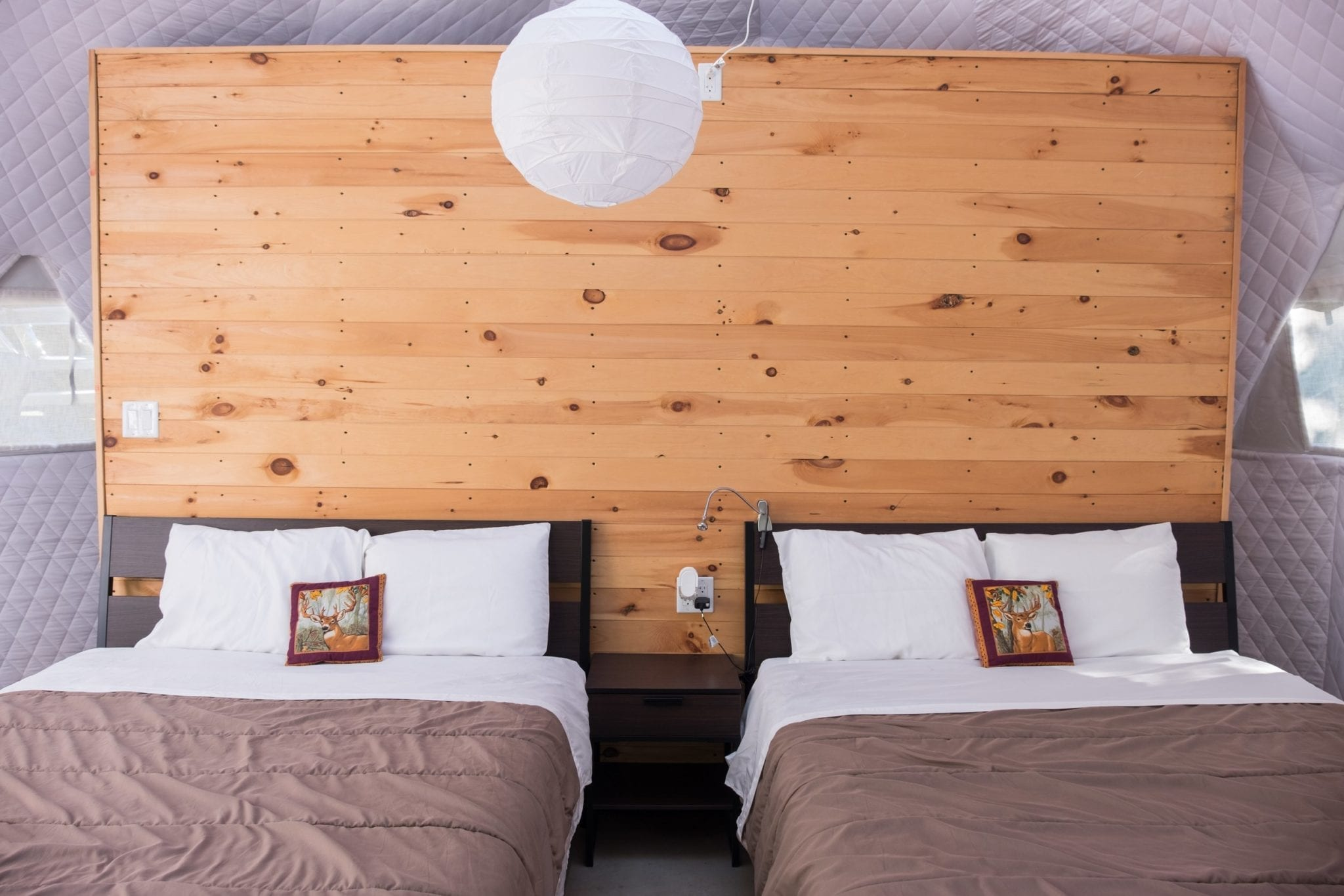 Two beds side by side with a wooden wall blinds them in the Blue Bayou Geodesic Domes