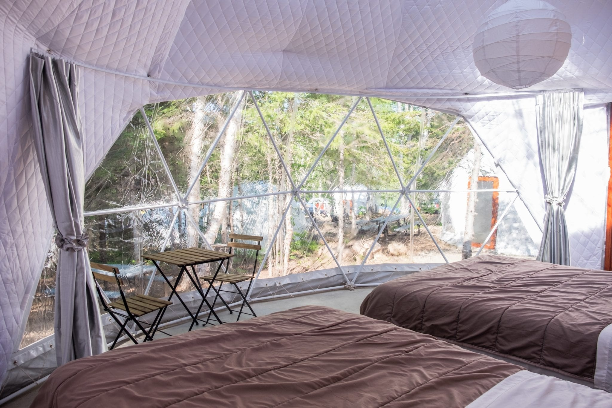 Two beds side by side in front of the triangular windows of the Blue Bayou Geodesic Domes