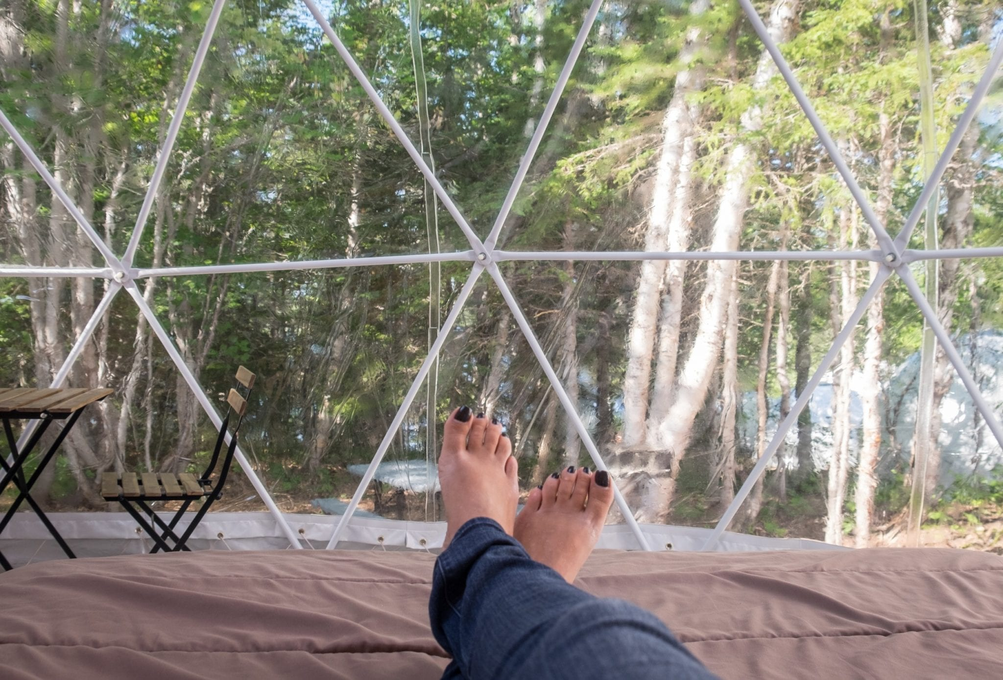 Kate's feet leaning off a bed in the Blue Bayou Geodesic Domes with the windows behind her feet and trees behind them.