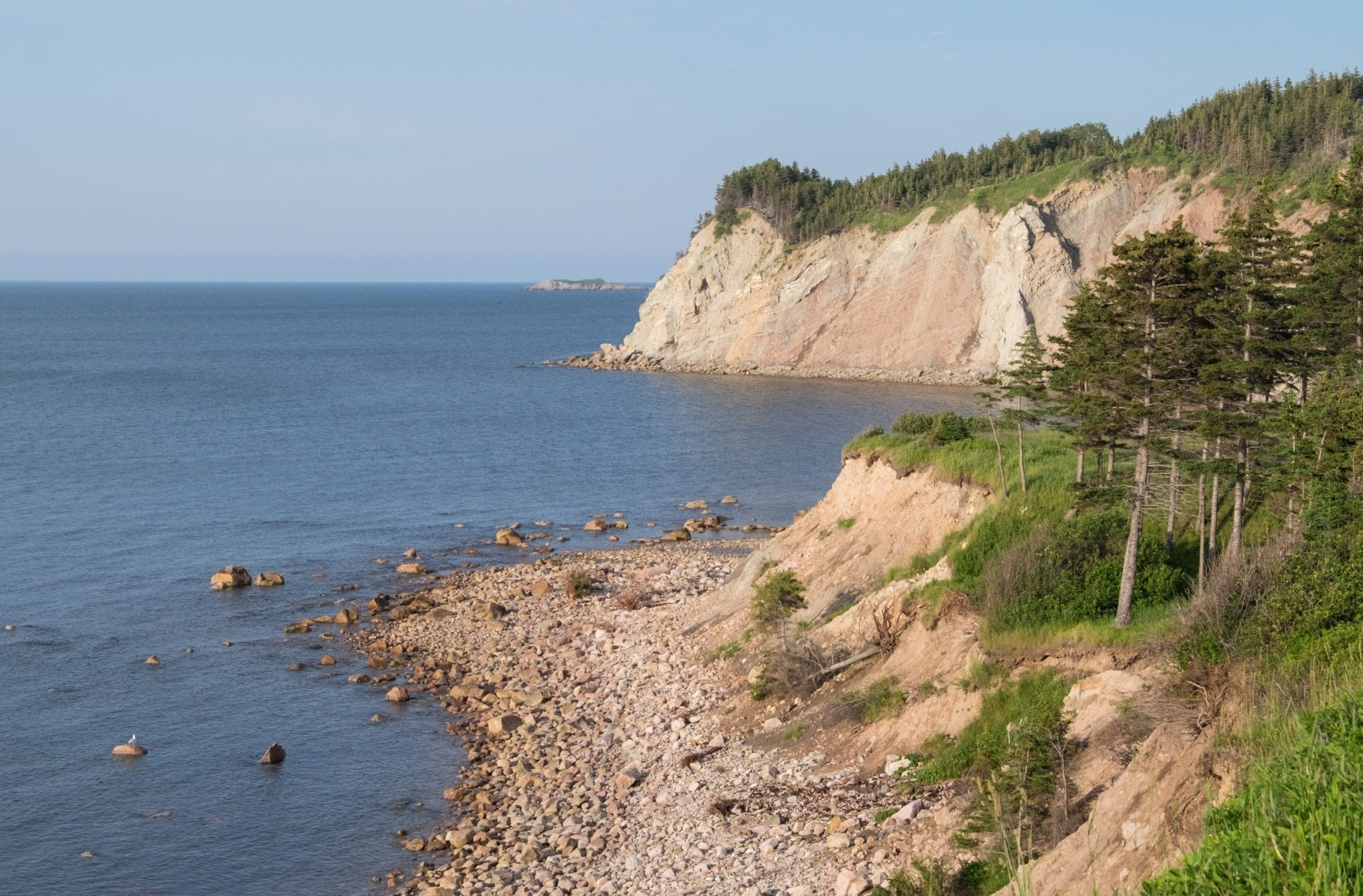 White limestone cliffs topped with grass plunging into the ocean in Cape Breton.