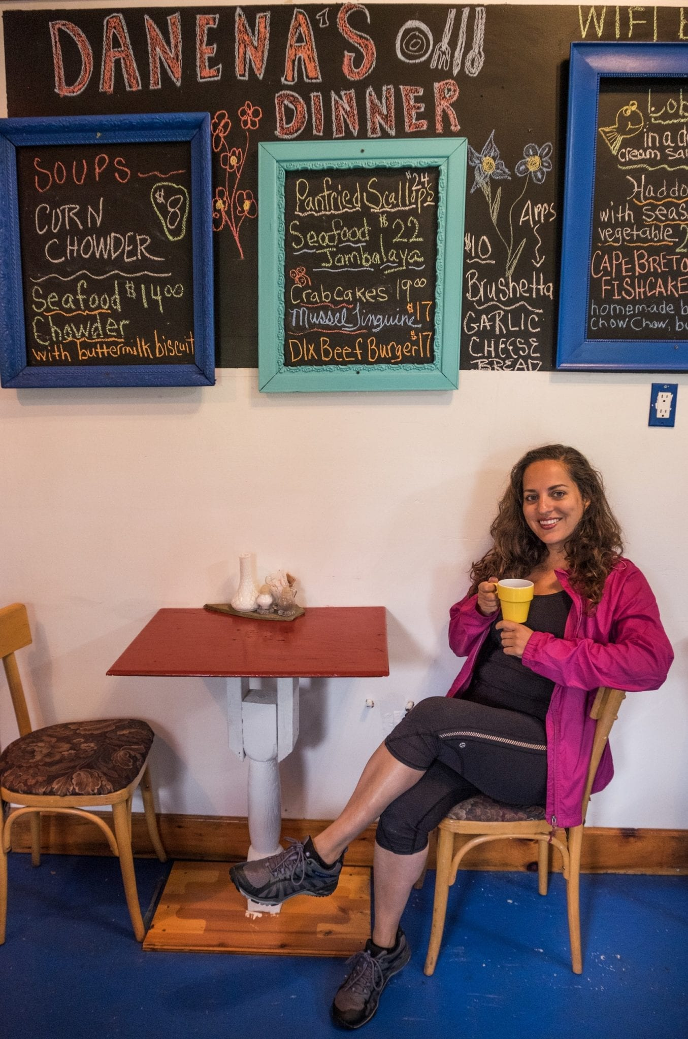 Kate wears a pink coat and smiles while holding a cup of coffee at a table beneath a blackboard detailing the restaurant's specials.