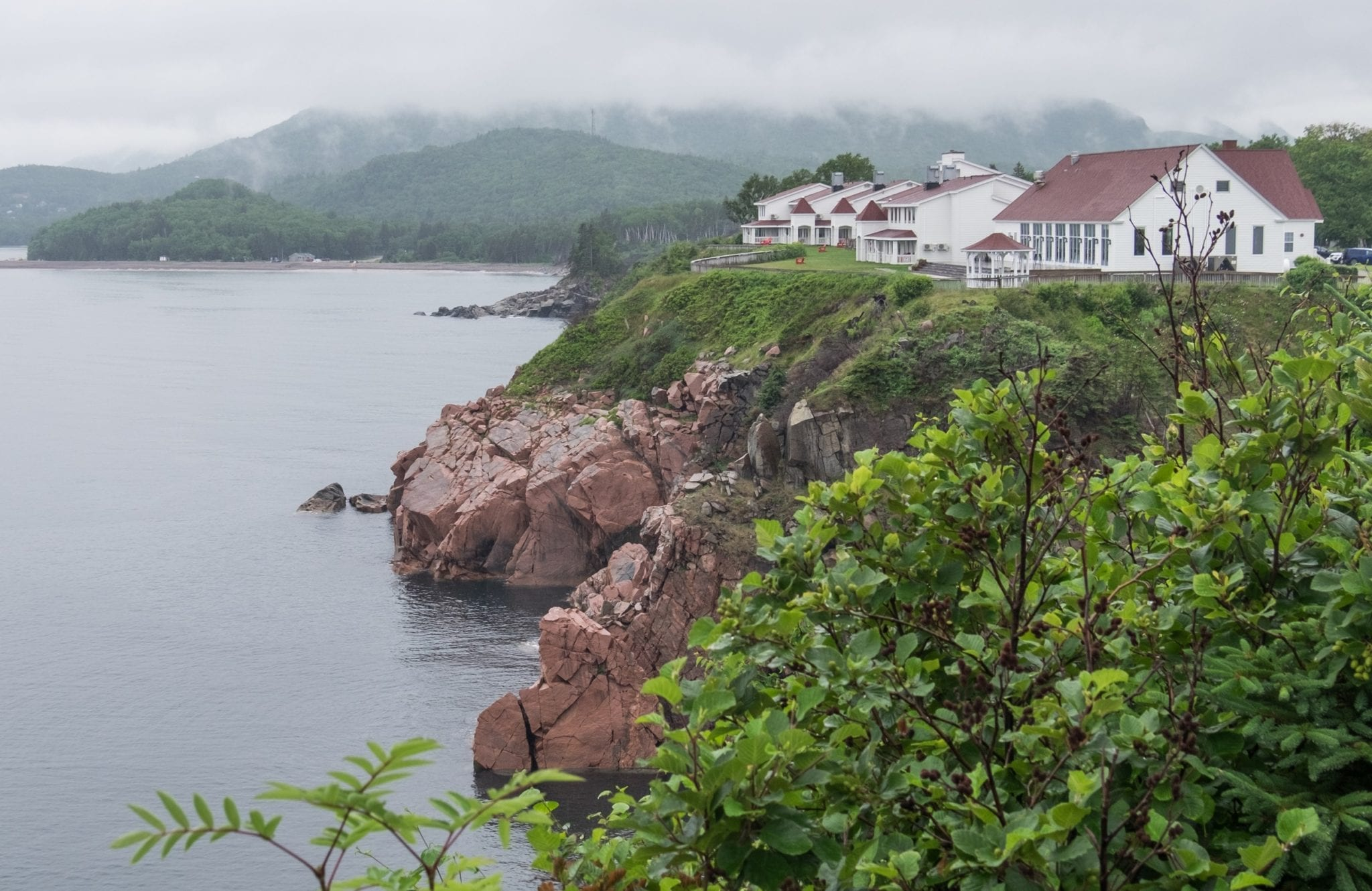 White cottages on top of red-brown cliffs among green vegetation, looking mysterious in the mist.