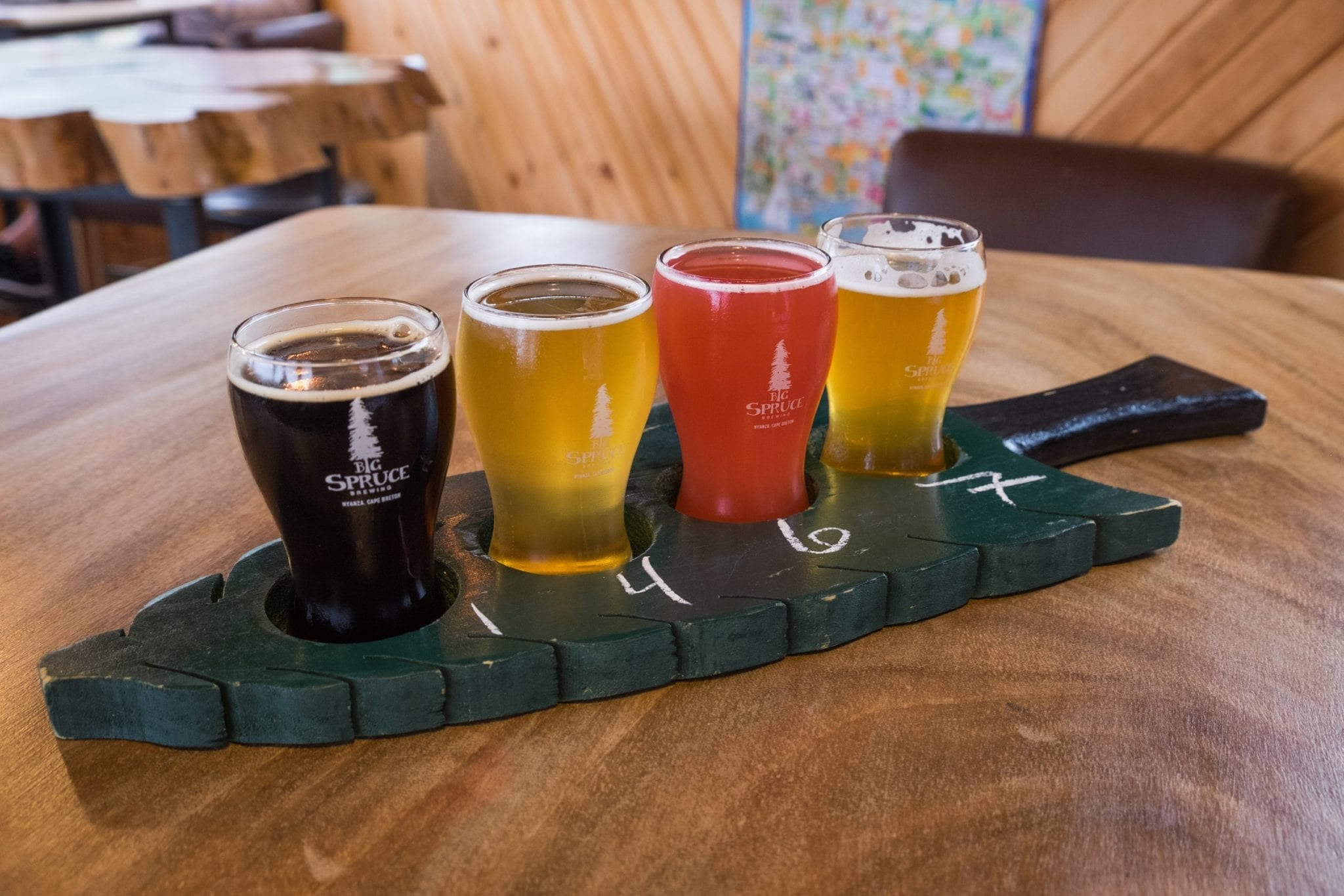 A spruce tree-shaped beer tray holding four small glasses of different beers.