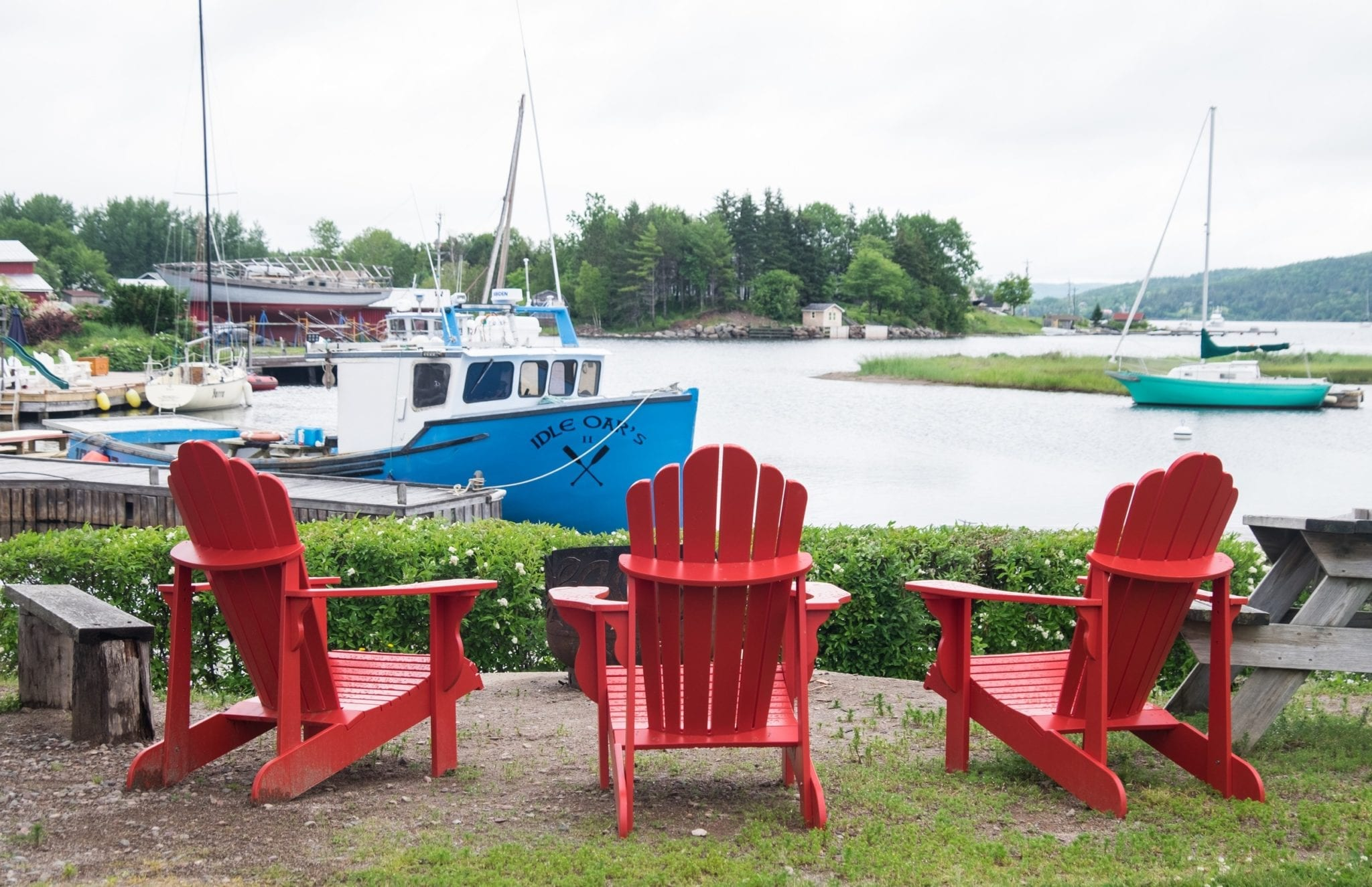 Three red chairs sitting in front of a blue boat a lake on an overcast day in Nova Scotia.
