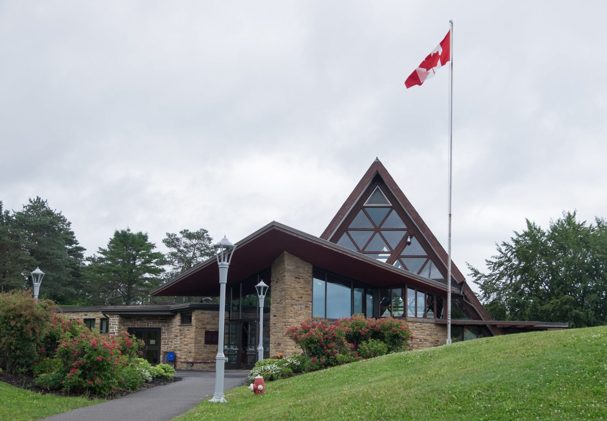 A modern triangular church-shaped building with a Canadian flag flying in front.