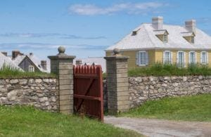 A stone wall has a red wooden gate open. There is a yellow building in the background underneath a blue sky streaked with white clouds. Louisberg, Nova Scotia.
