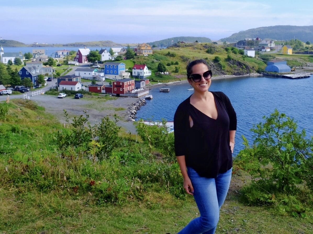 Kate stands in front of a panorama of Trinity, Newfoundland: green hills with brightly colored cottages next to the sea.