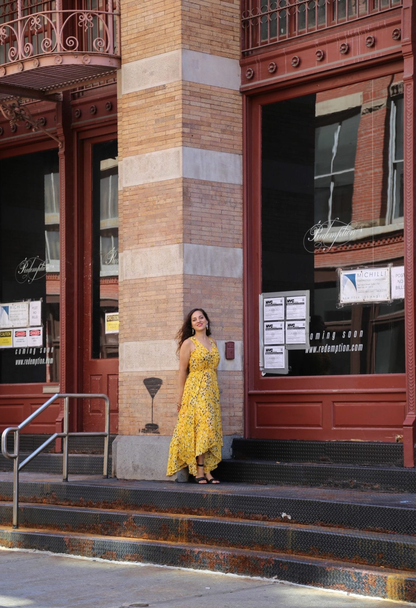 Kate standing in front of a column in a yellow dress in SoHo, NYC.