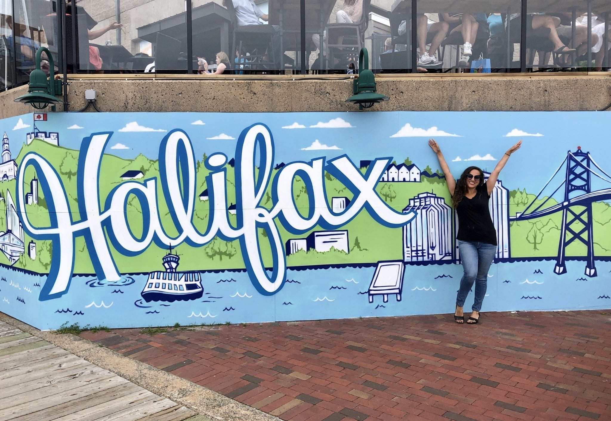 Kate poses with her arms in the air in front of a blue, green and white mural with the word Halifax in front of the Halifax cityscape.