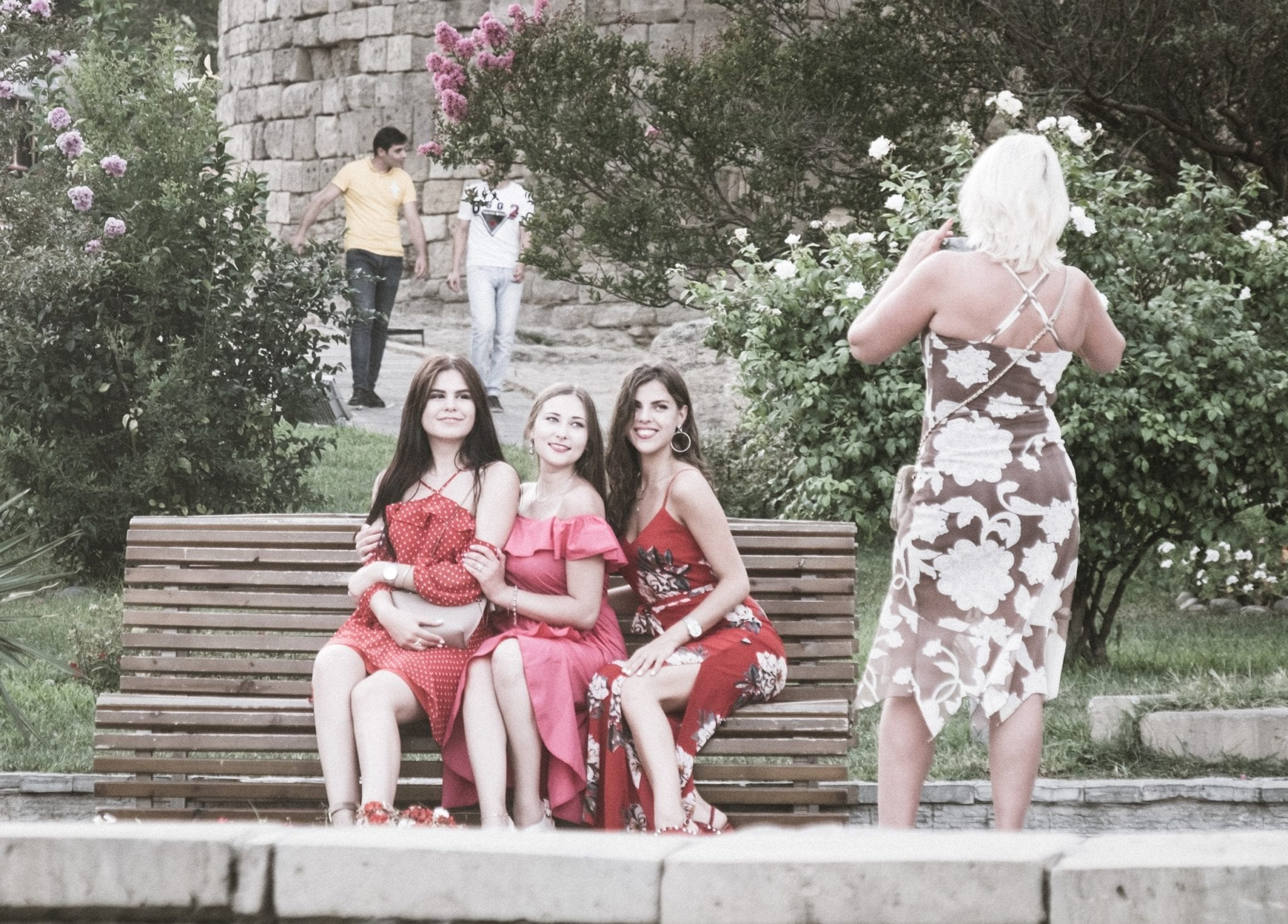 Three teenage girls in pink and red dresses sitting on a bench in the old city of Baku as a woman takes their photo.