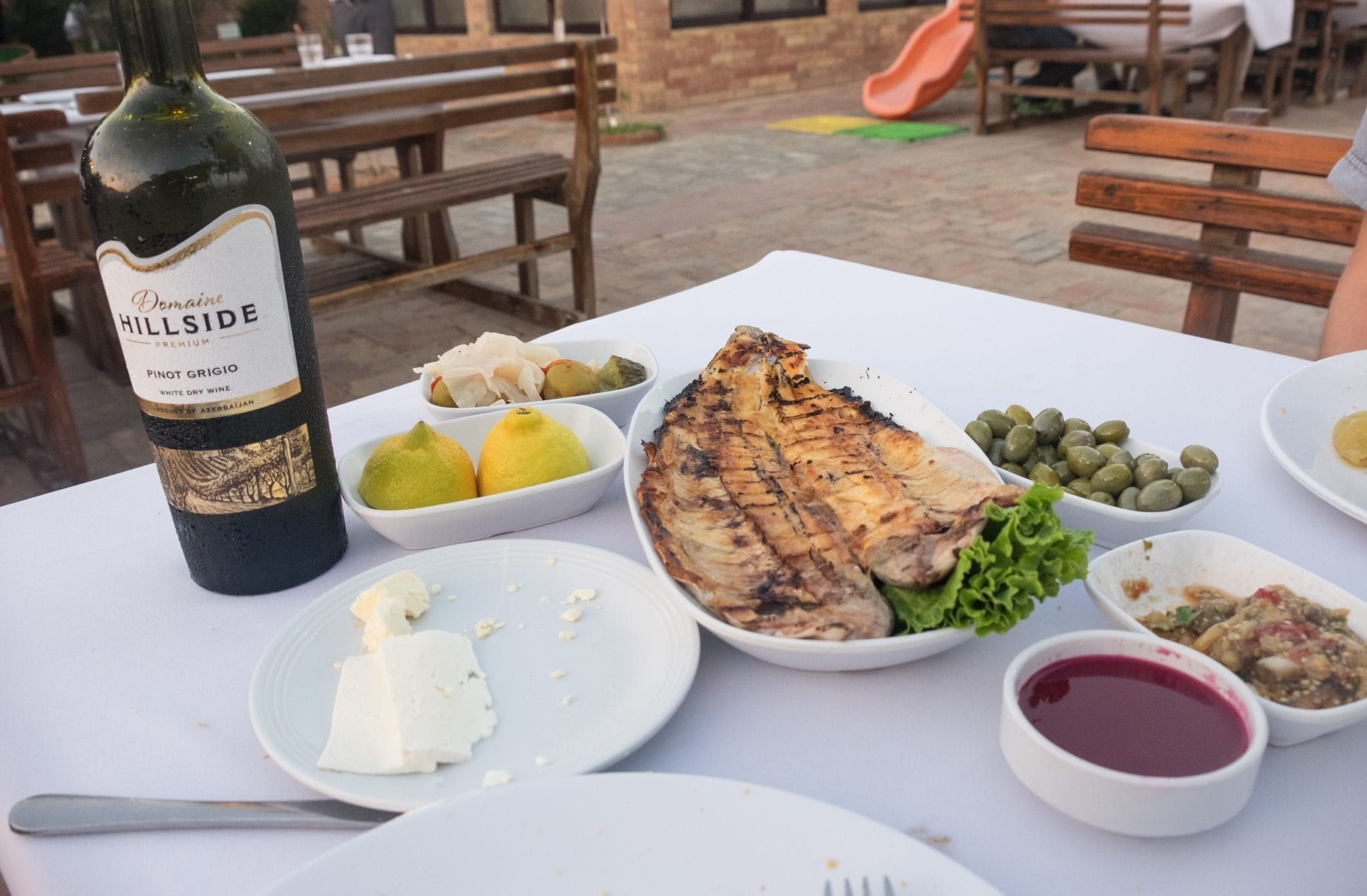 A meal at Derya Fish house: fish, wine, and several vegetable dishes and bread.