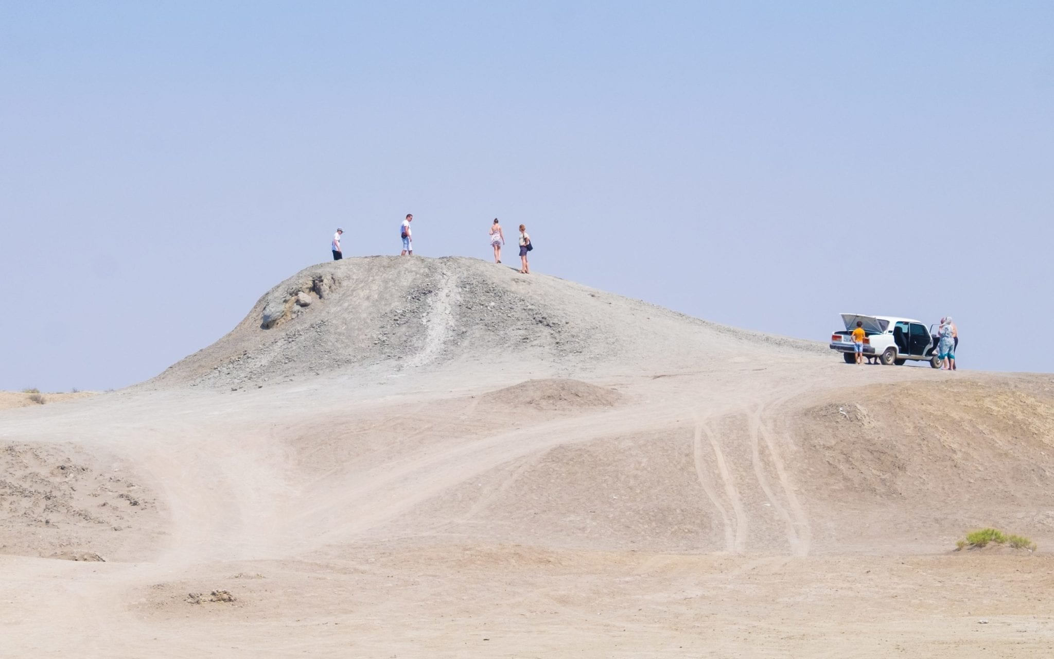 Four tiny people standing atop a mud volcano in the desert, making it look enormous.