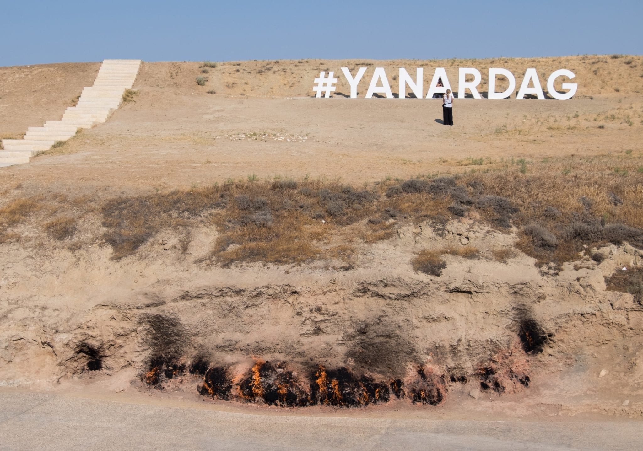 A brown hillside at Yanar Dag where flames burst out of the earth at the bottom. It says #YANARDAG in white on the hill, in the style of the Hollywood sign.